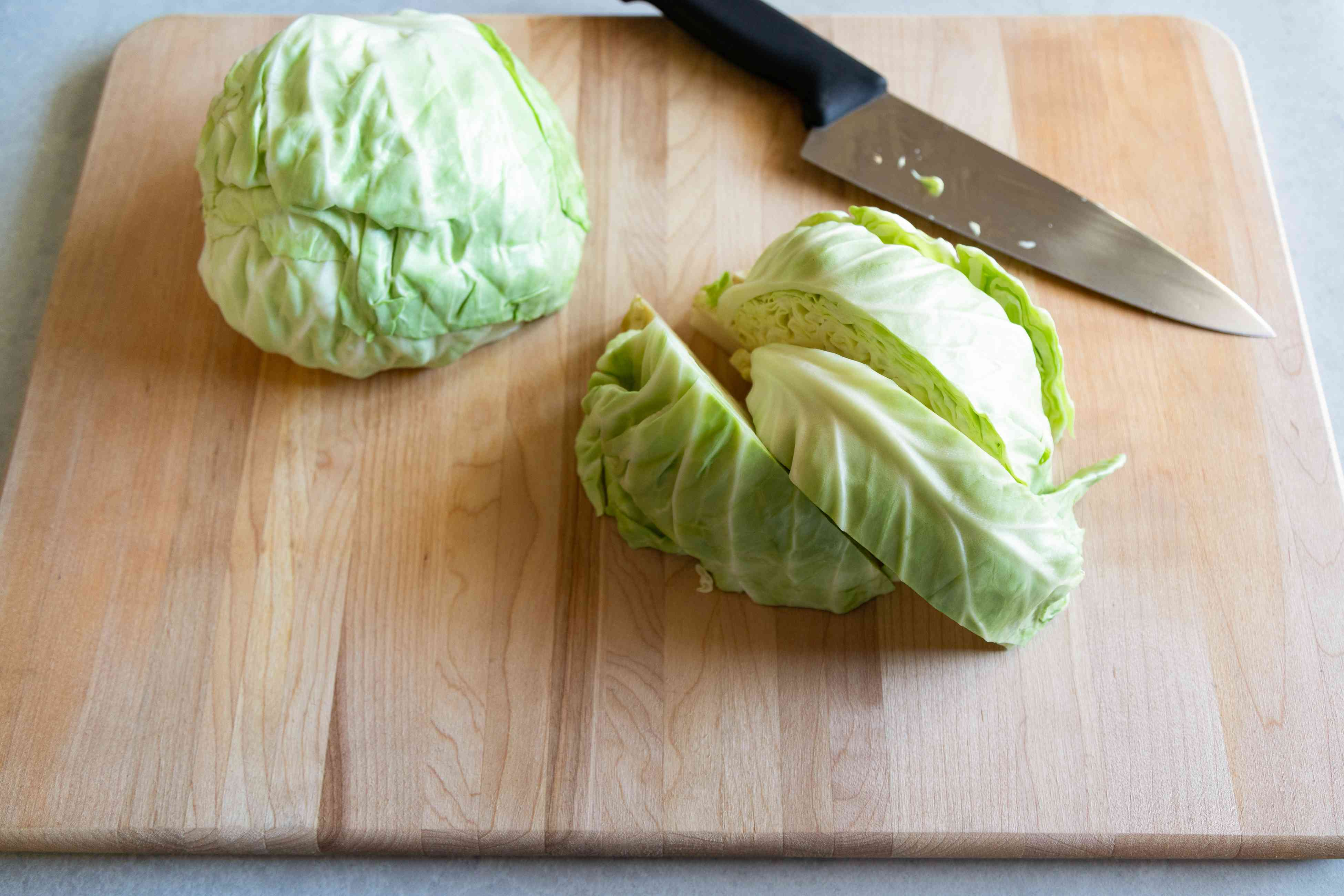 Chopping cabbage into wedges for grilled cabbage with peanut satay sauce.