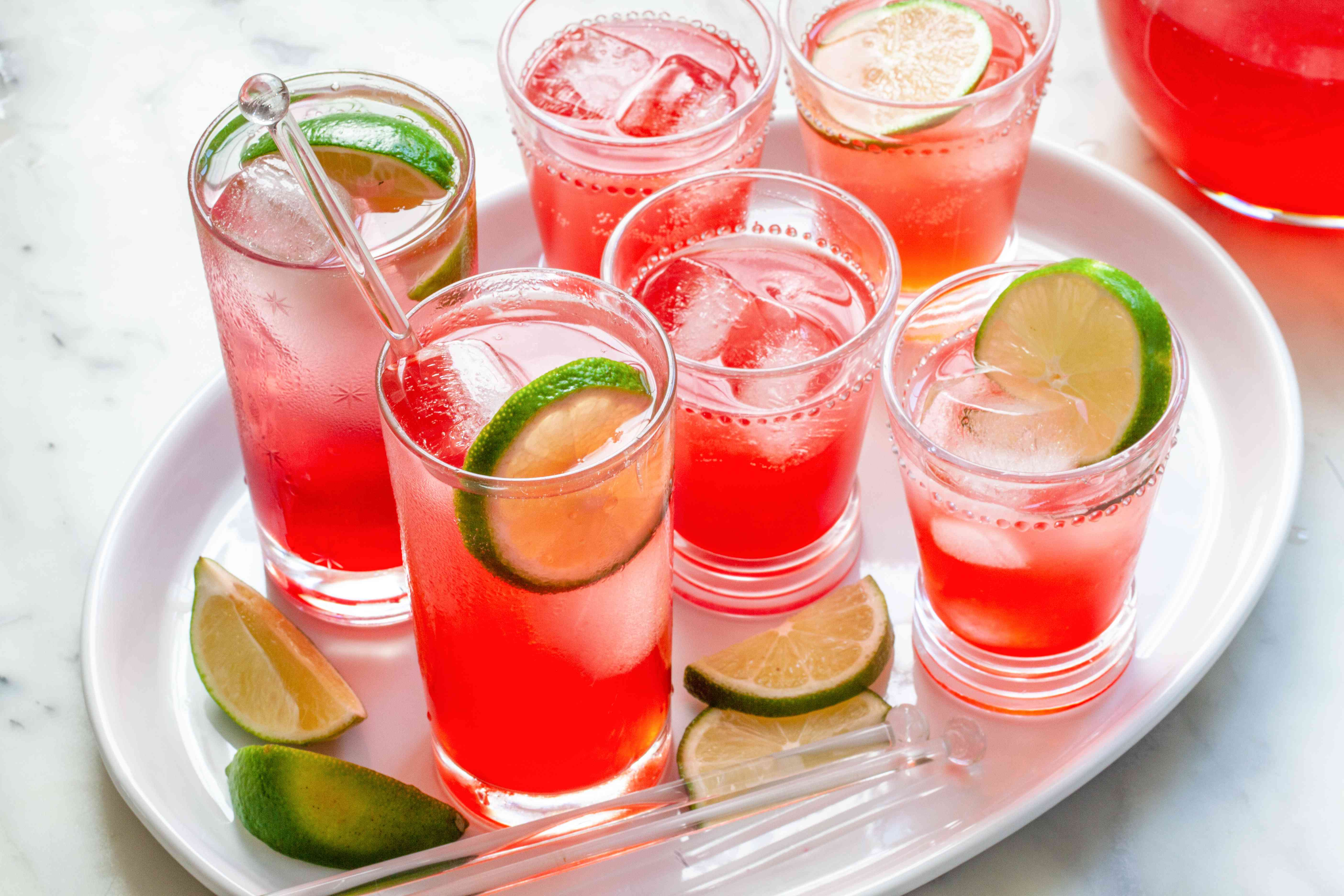 Highball glasses of raspberry lime rickey set on a tray.