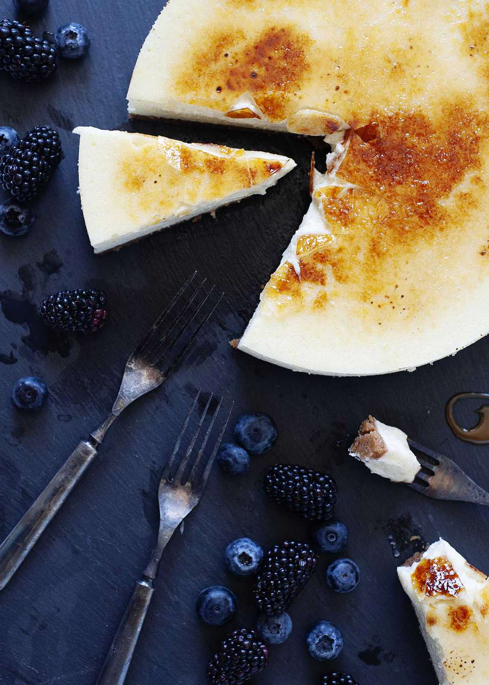 Vanilla Bean Cheesecake with brittle sugar topping on a slate board wtih a slice cut out and fruit and forks nearby.