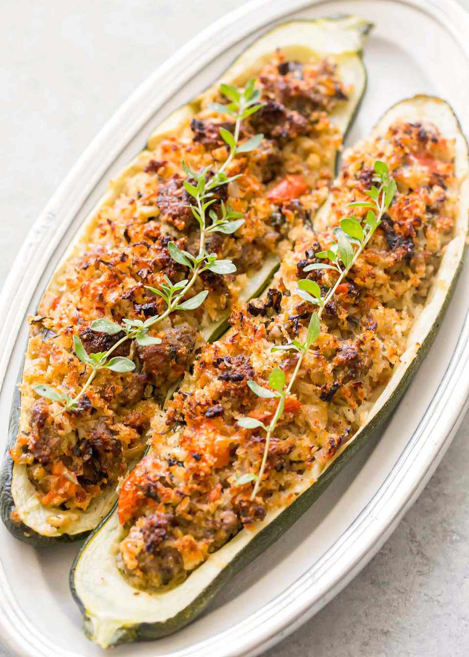 Sausage stuffed zucchini on a platter and topped with a sprig of herbs.