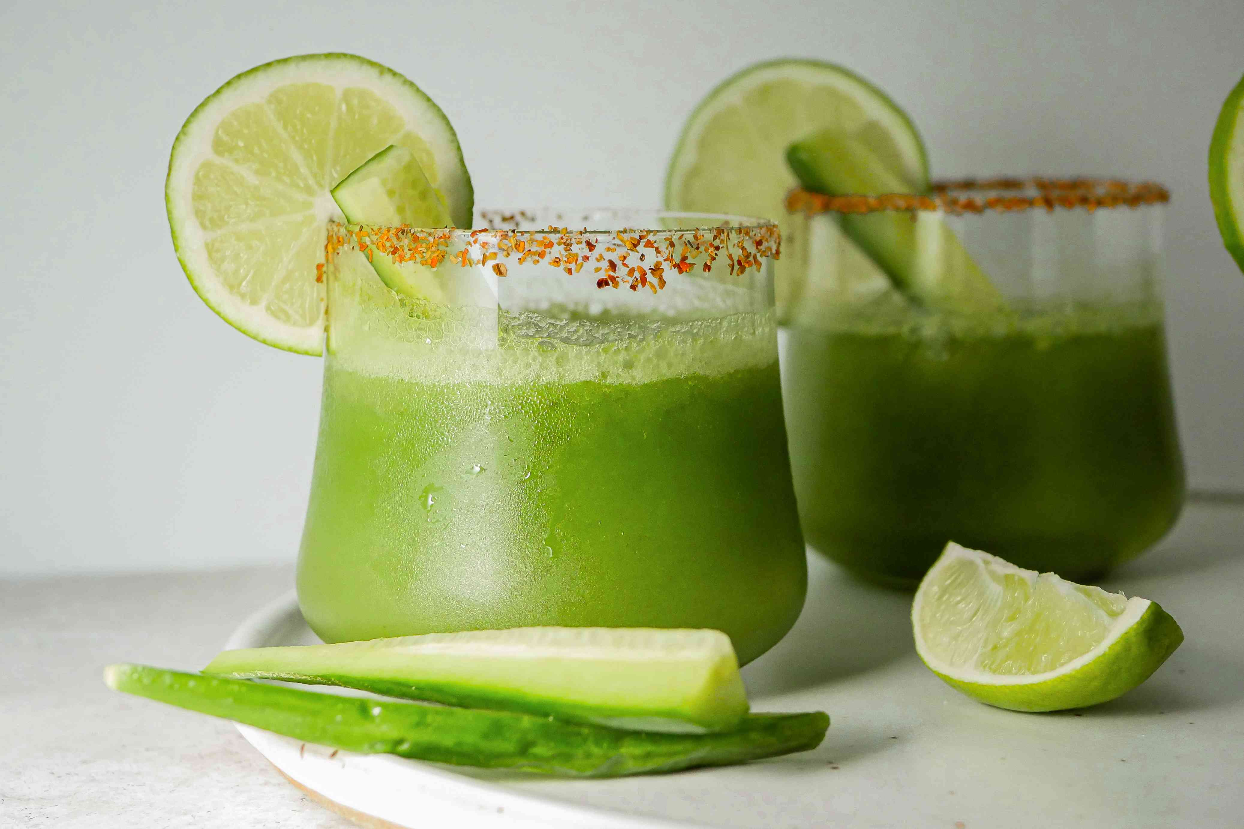 Two glasses of pitcher cucumber margaritas garnished with lime and cucumber.