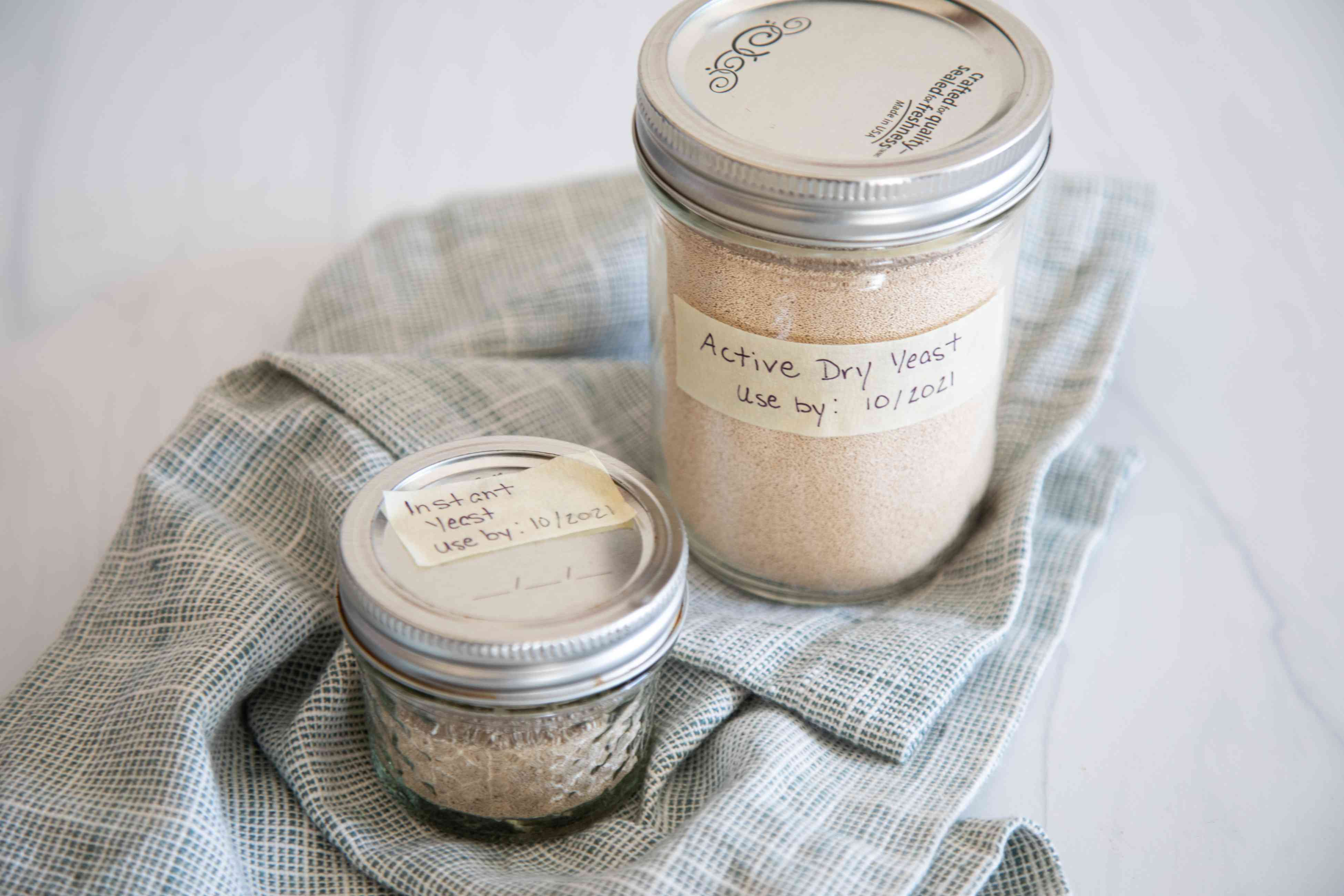 Mason jars with yeast inside set on a linen to show how to store yeast.