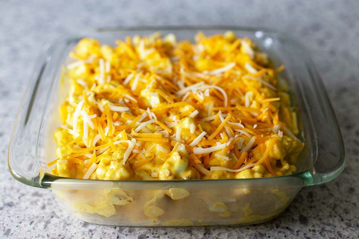 Shredded cheese tops a casserole dish with Baked Cheesy Cauliflower inside.