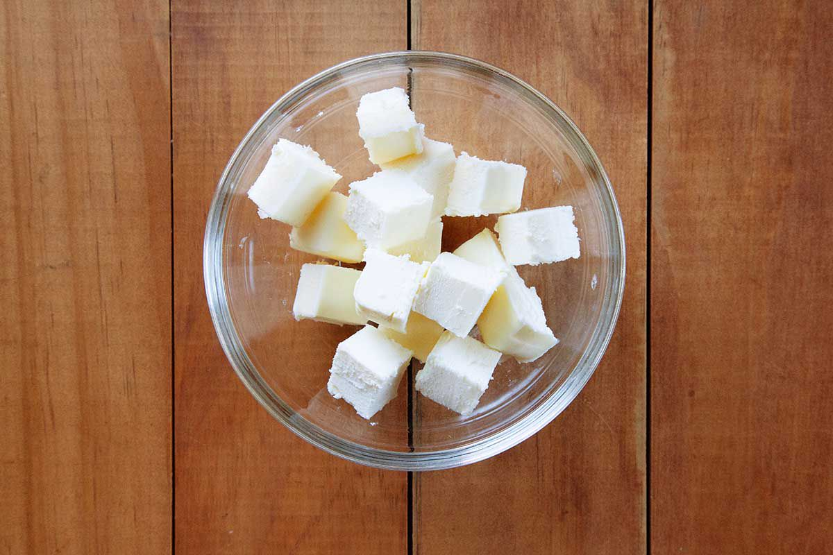 Cubed butter in a small glass dish and sitting on a wooden table.