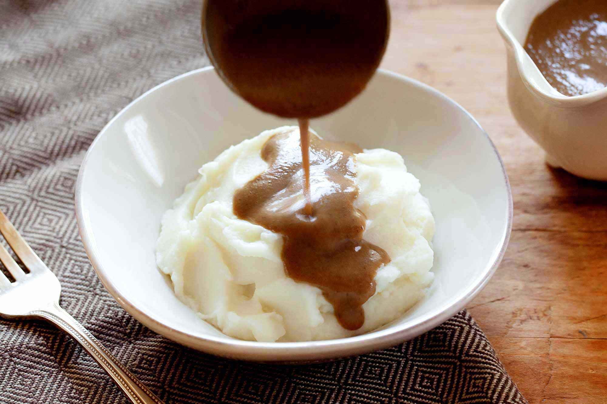 Easy Vegan mushroom gravy poured over a pile of mashed potatoes on a white bowl.