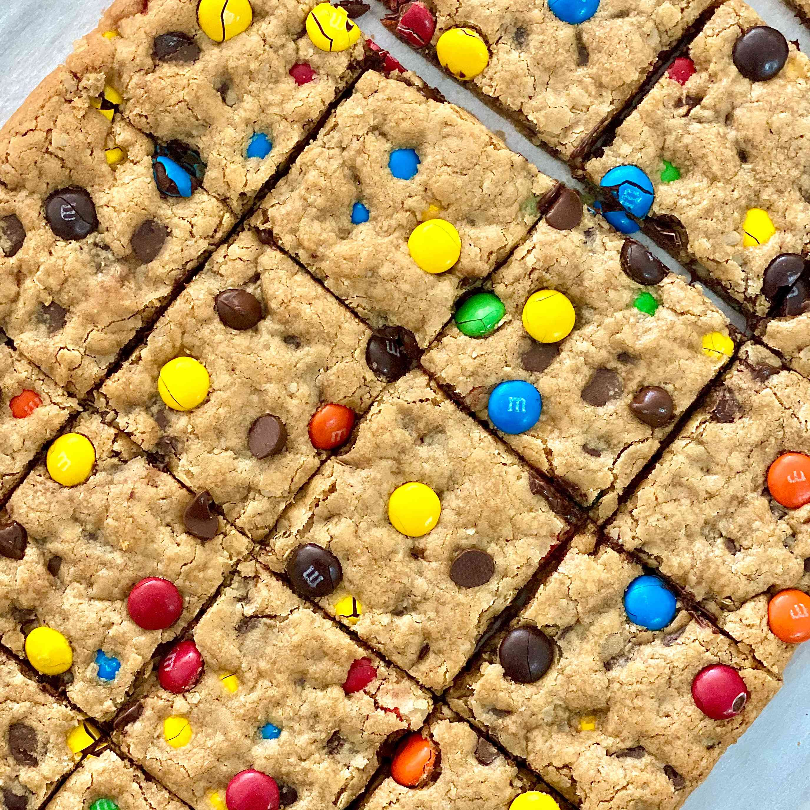 The BEST GF Monster Cookie Recipe sliced into squares and set on parchment paper.