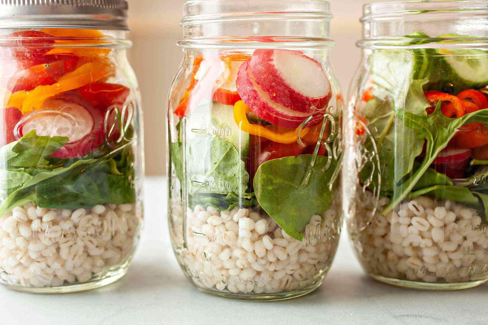 How To Cook Barley - three open jars of grains and veggies