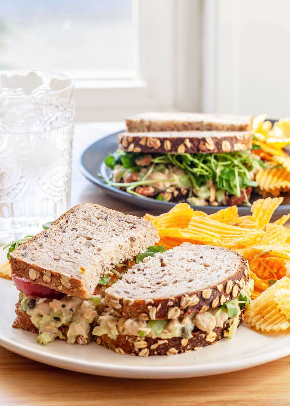 Side view of a vegetarian chickpea sandwich on plate with chips. A second plate and sandwich are behind it.