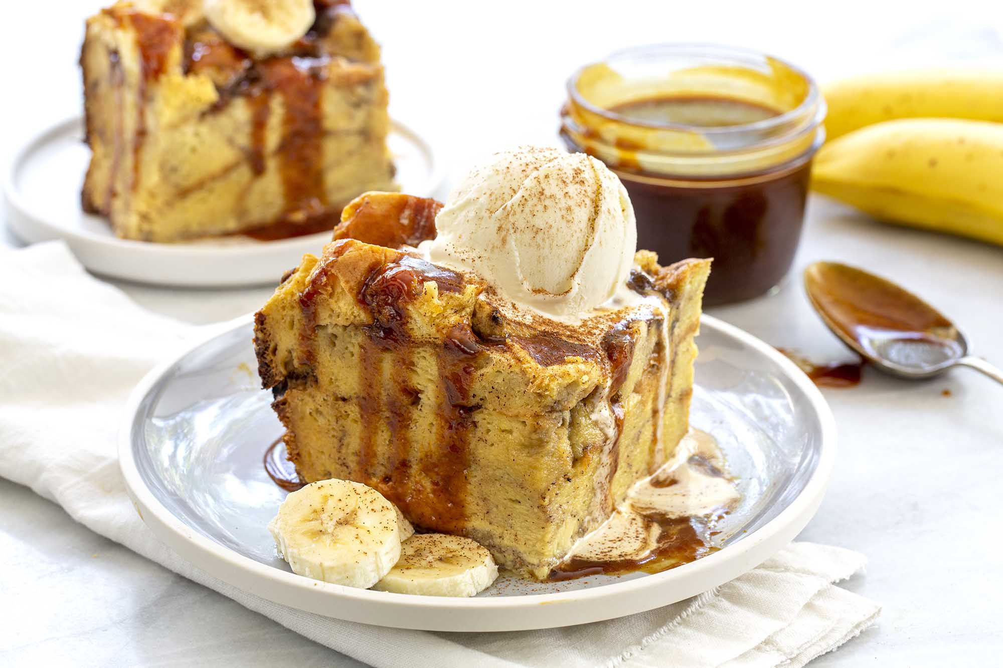 Slice of the best slow cooker banana bread pudding topped with a scoop of ice cream and drizzeld with caramel sauce on a gray plate. A jar of caramel sauce is off to the side.