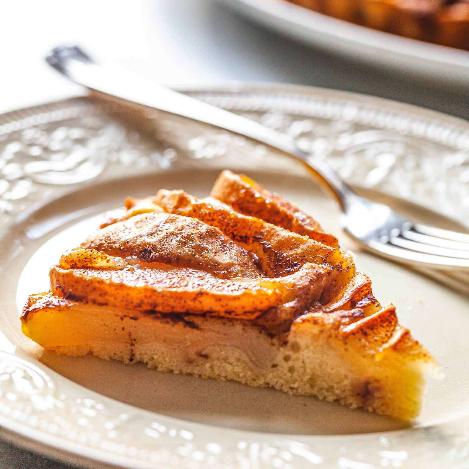 Slice of homemade pear cake on a plate with a fork.