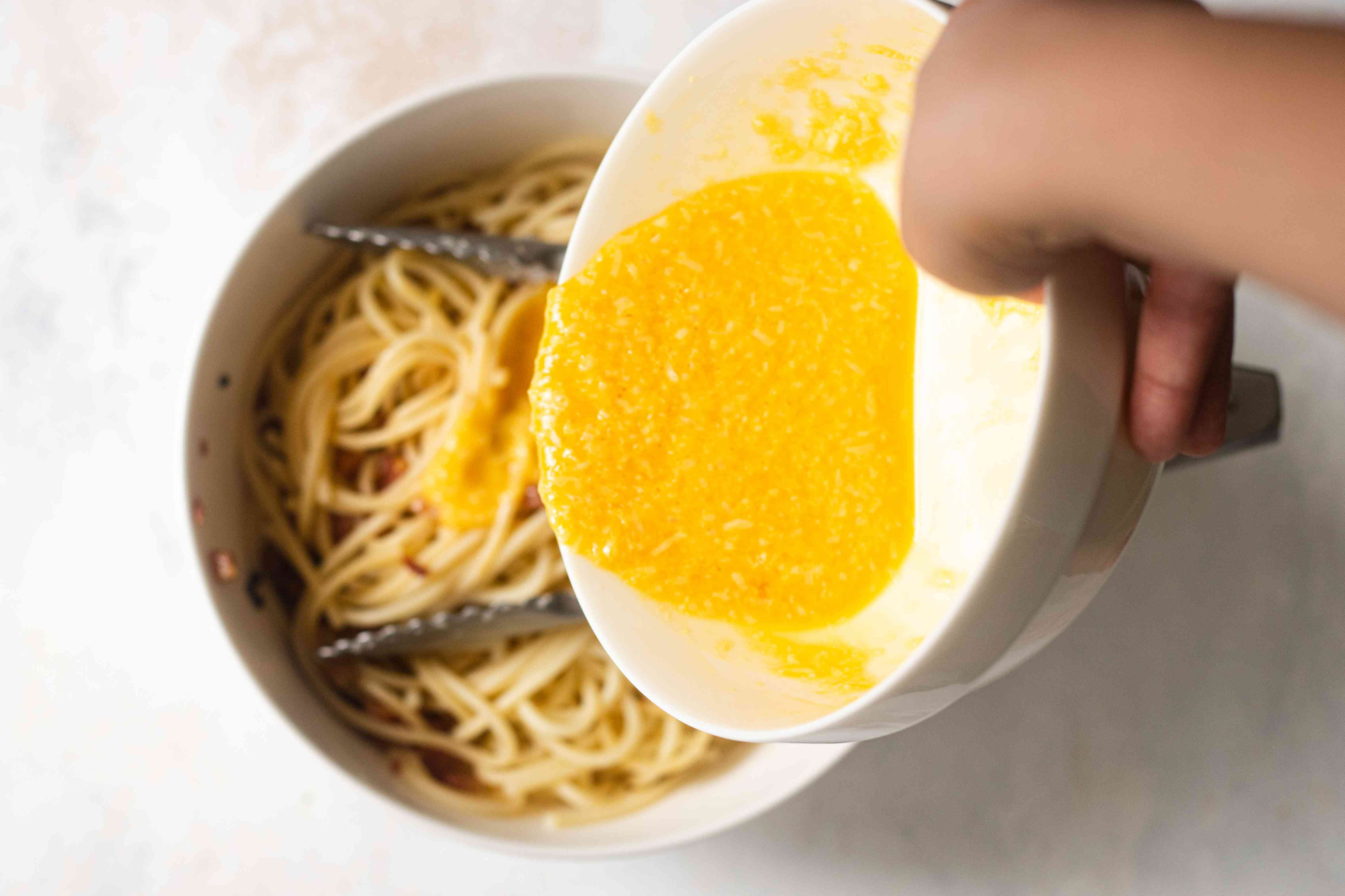 Adding whisked eggs to a bowl of noodles for Spaghetti Carbonara.