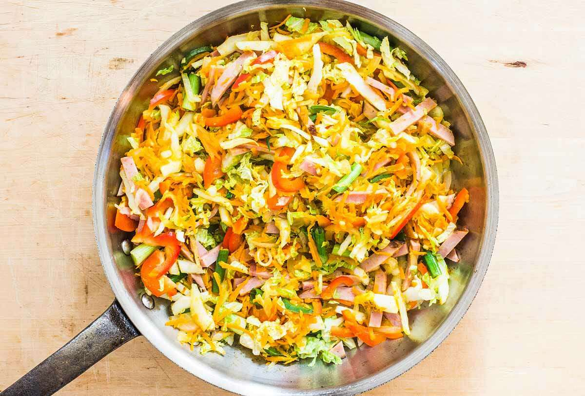 combine together the noodles, eggs, and vegetables for Singapore Street Noodles
