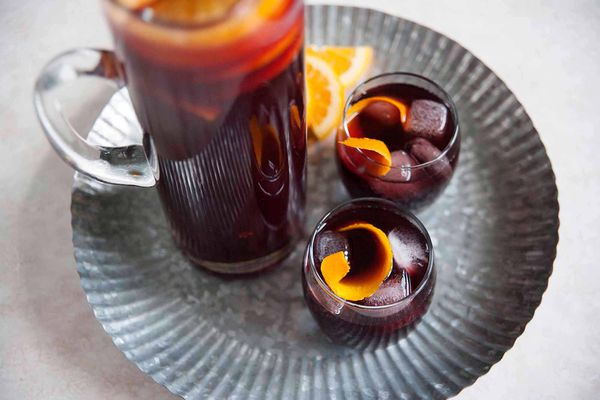 Best Fruity Sangria Recipe - orange slices in a pitcher of sangria on a silver tray with two poured glasses of sangria