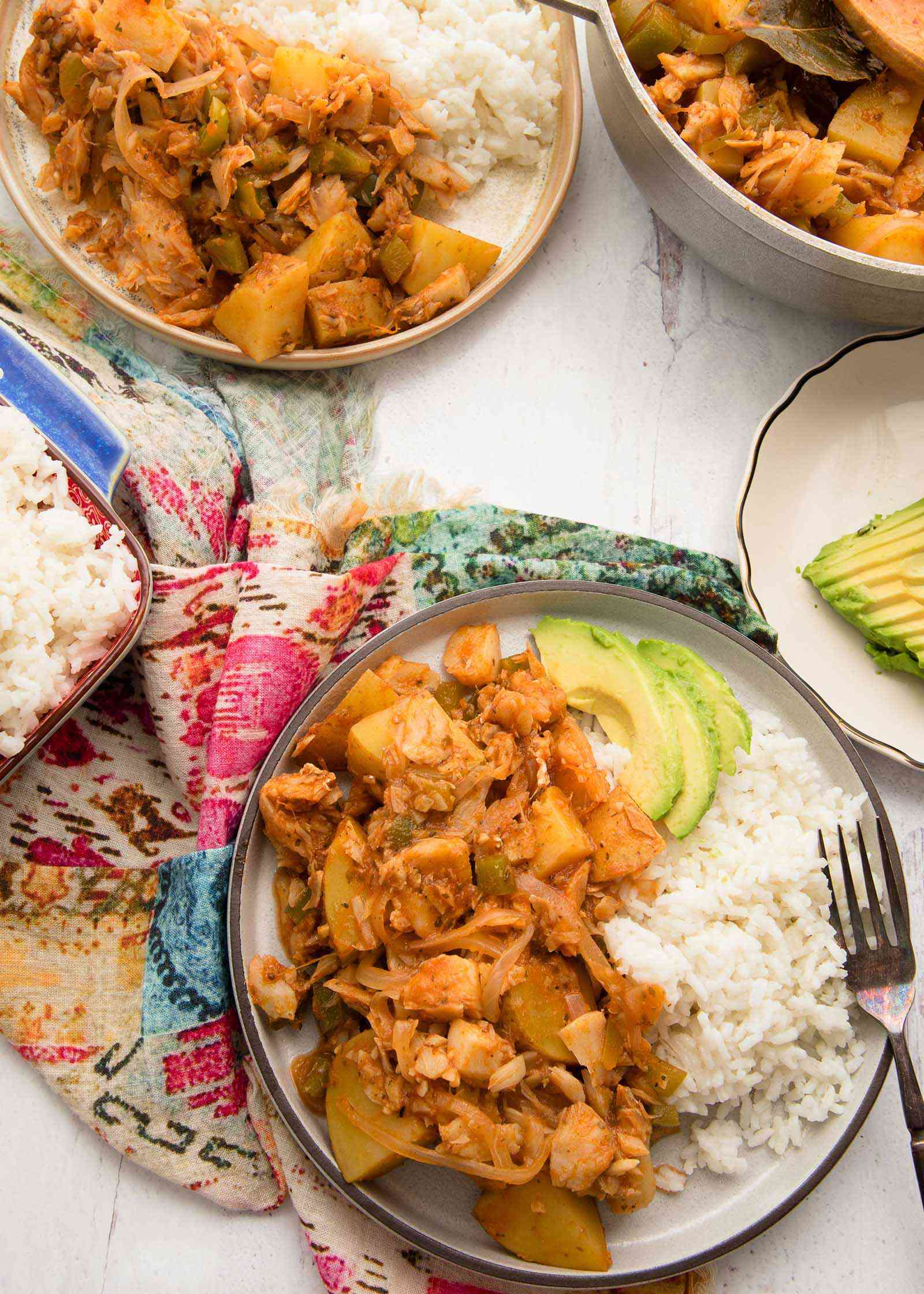 Overhead view of a rimmed plate with Puerto Rican Stewed Fish on the left side and sliced avocado and white rice on the right. A fork is on the plate to the right as well. Above the plate is small plate in partial view with sliced avocado on it. Above the avocado is a dutch oven with Lenten Cod recipe in partial view. To the left of the dutch oven is another rimmed plate with stewed codfish and white rice. A bright patterened linen is underneath the plate and white rice is in a blue casserole dish in partial view.