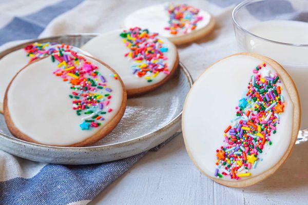 Royal icing and sprinkles decorate circle sugar cookies.