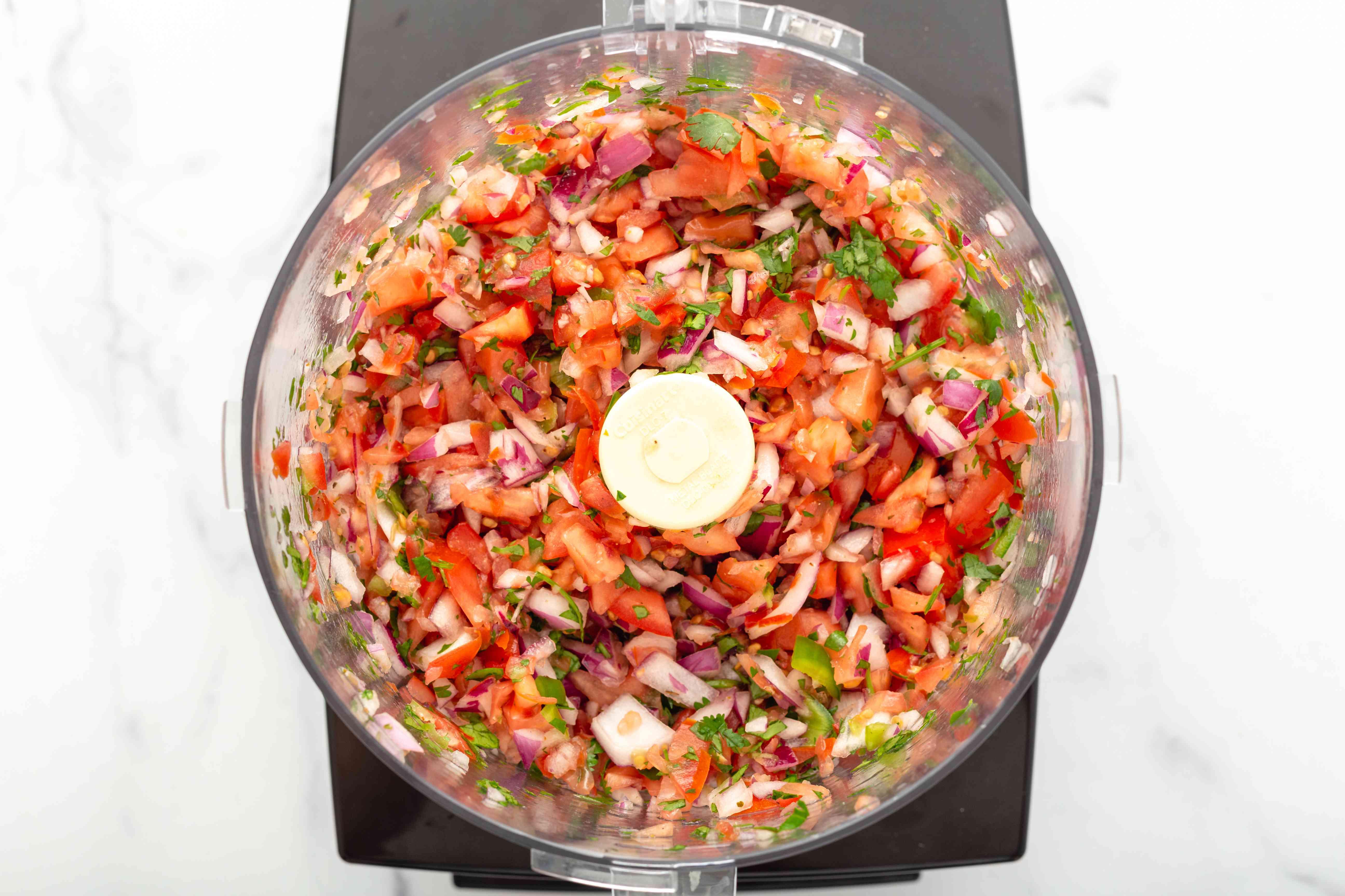 Food processor with pico de gallo inside.