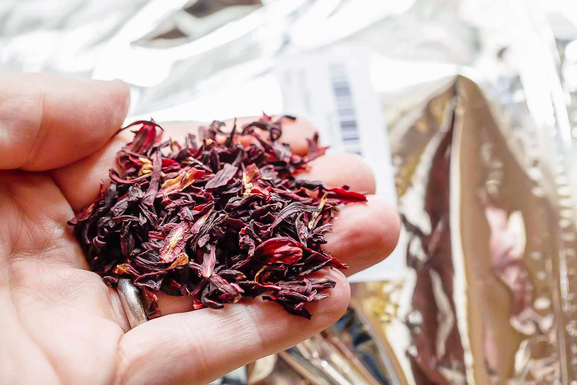 Dried hibiscus is displayed on the palm of a hand. The hand is held above the plastic containers it came in.