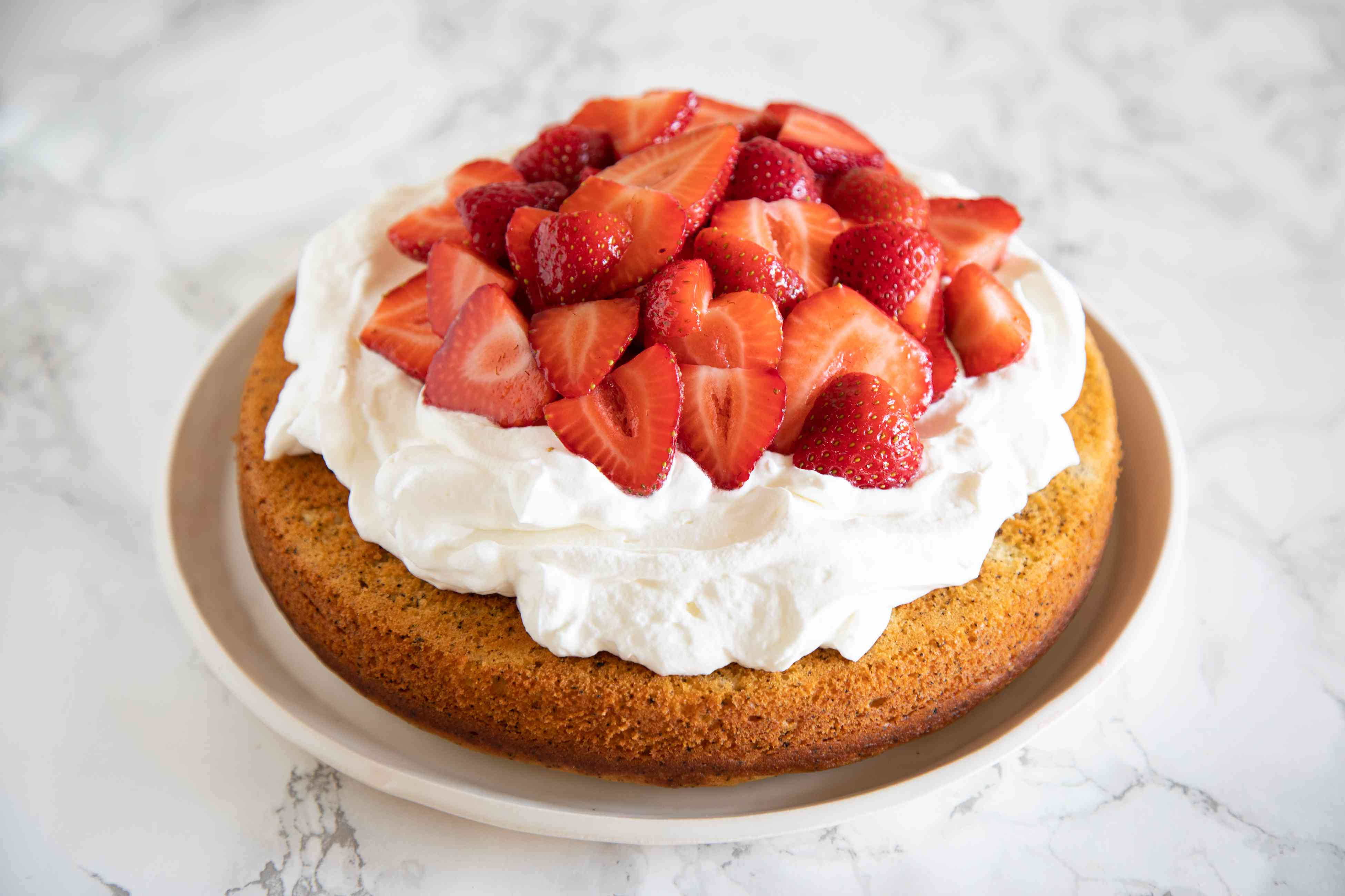 Earl Grey Tea Yogurt Cake topped with whipped cream and strawberries and set on a platter.
