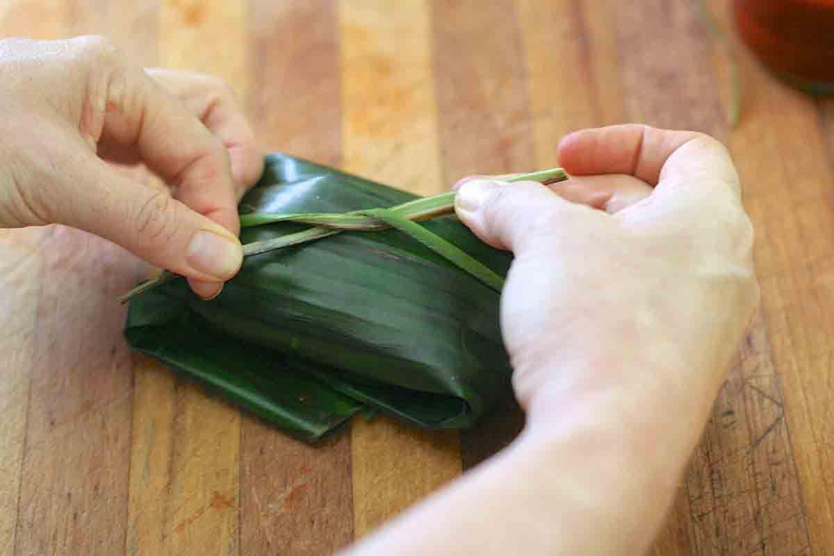 tying a banana leaf tamale
