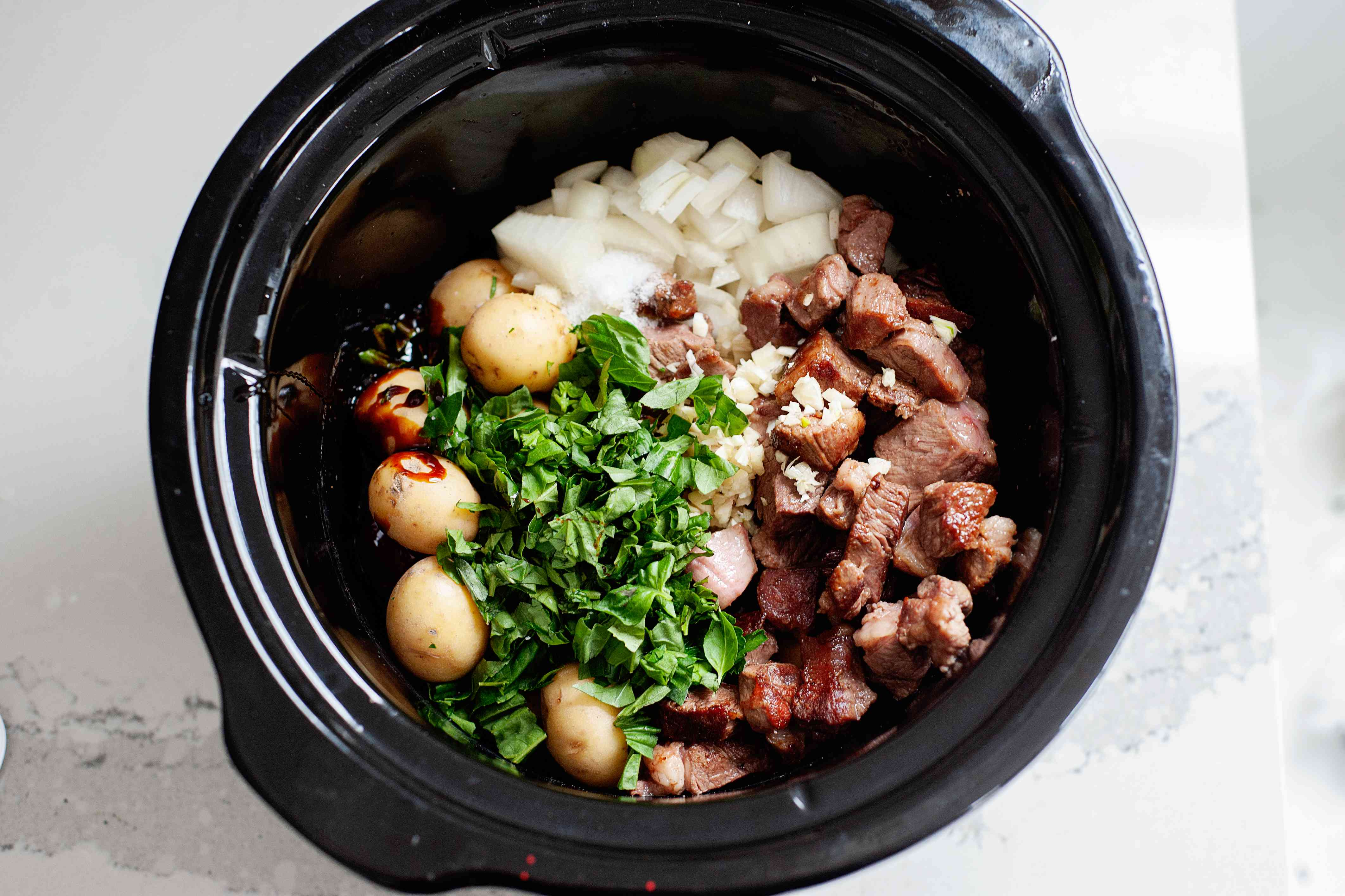 Ingredients for Weekday Lamb Stew inside a slow cooker.