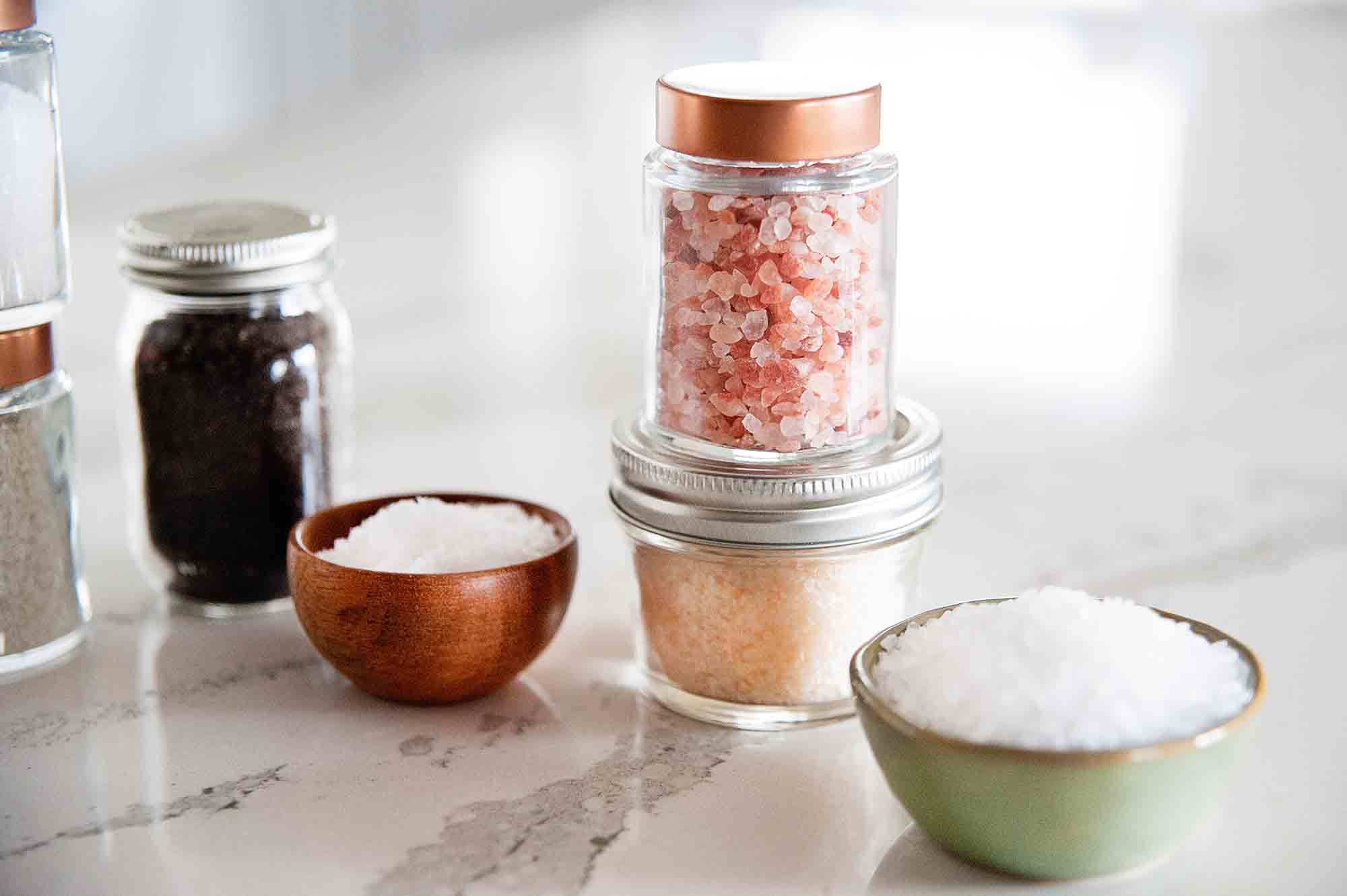 Jars and bowls of kosher salt, Himalyan salt, and smoked salt