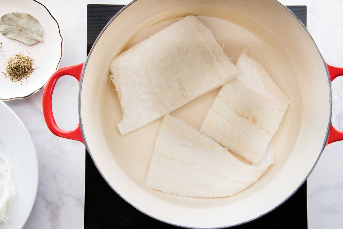 Three fillets of salt cod are at the bottom of a dutch oven. A scalloped plate has a bay leaf and ground spices to the left of the pot.