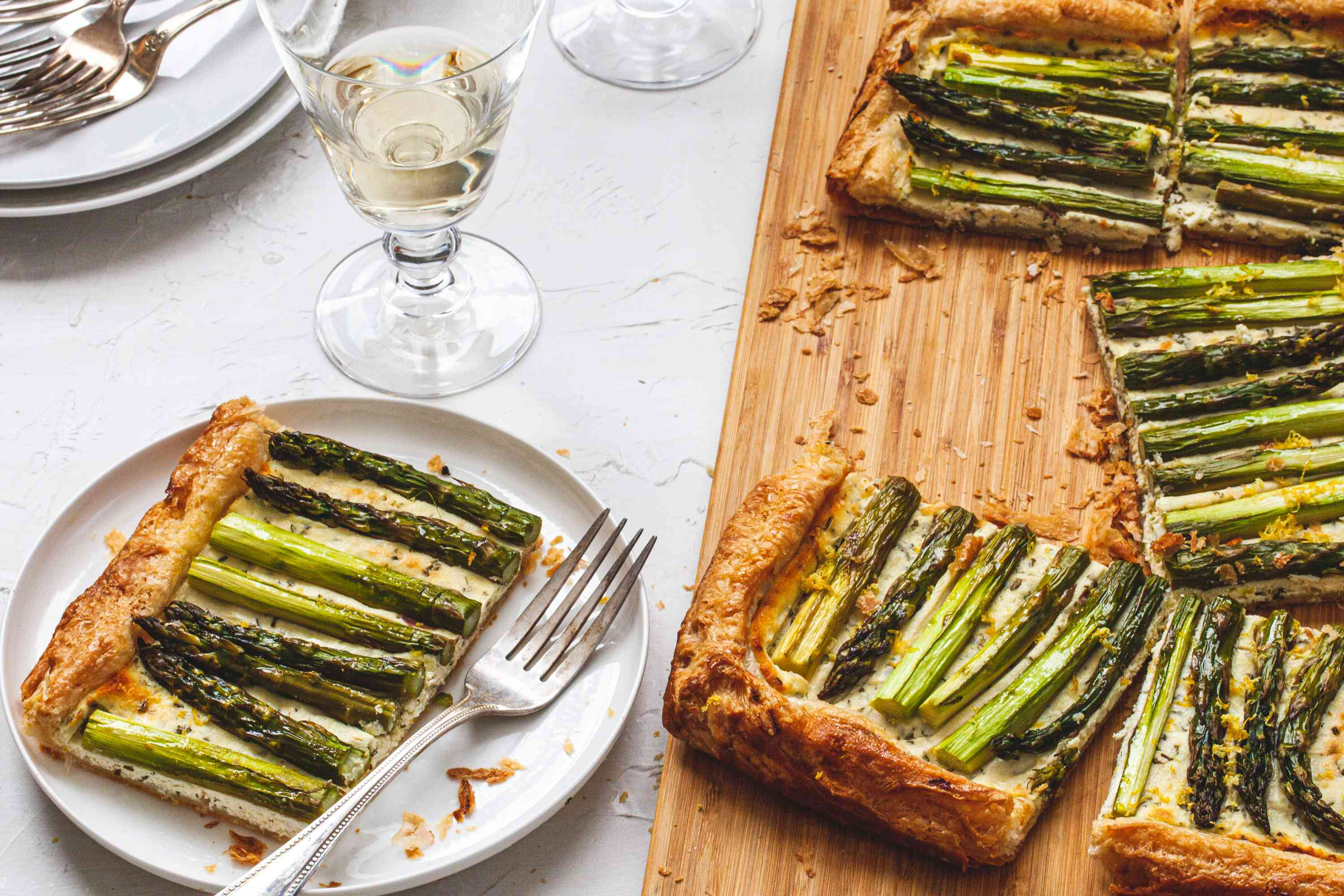Easy Asparagus Tart on a cutting board and a piece served on a plate.