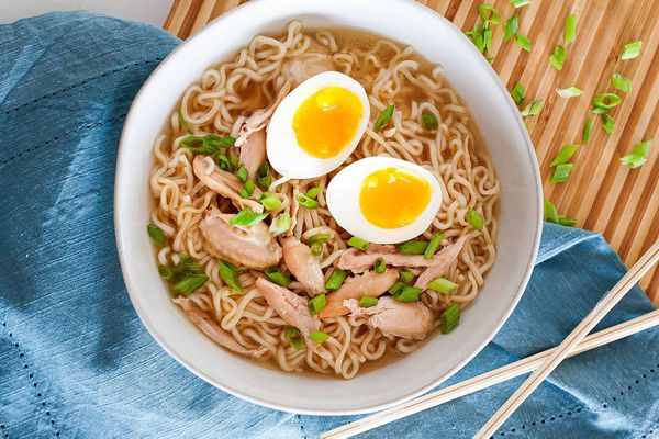 A white bowl, sitting next to a blue napkin on a cutting board. The bowl is filled with the best chicken wing ramen. It has noodles, chicken, scallions, and a soft boiled egg -- all made in the pressure cooker.