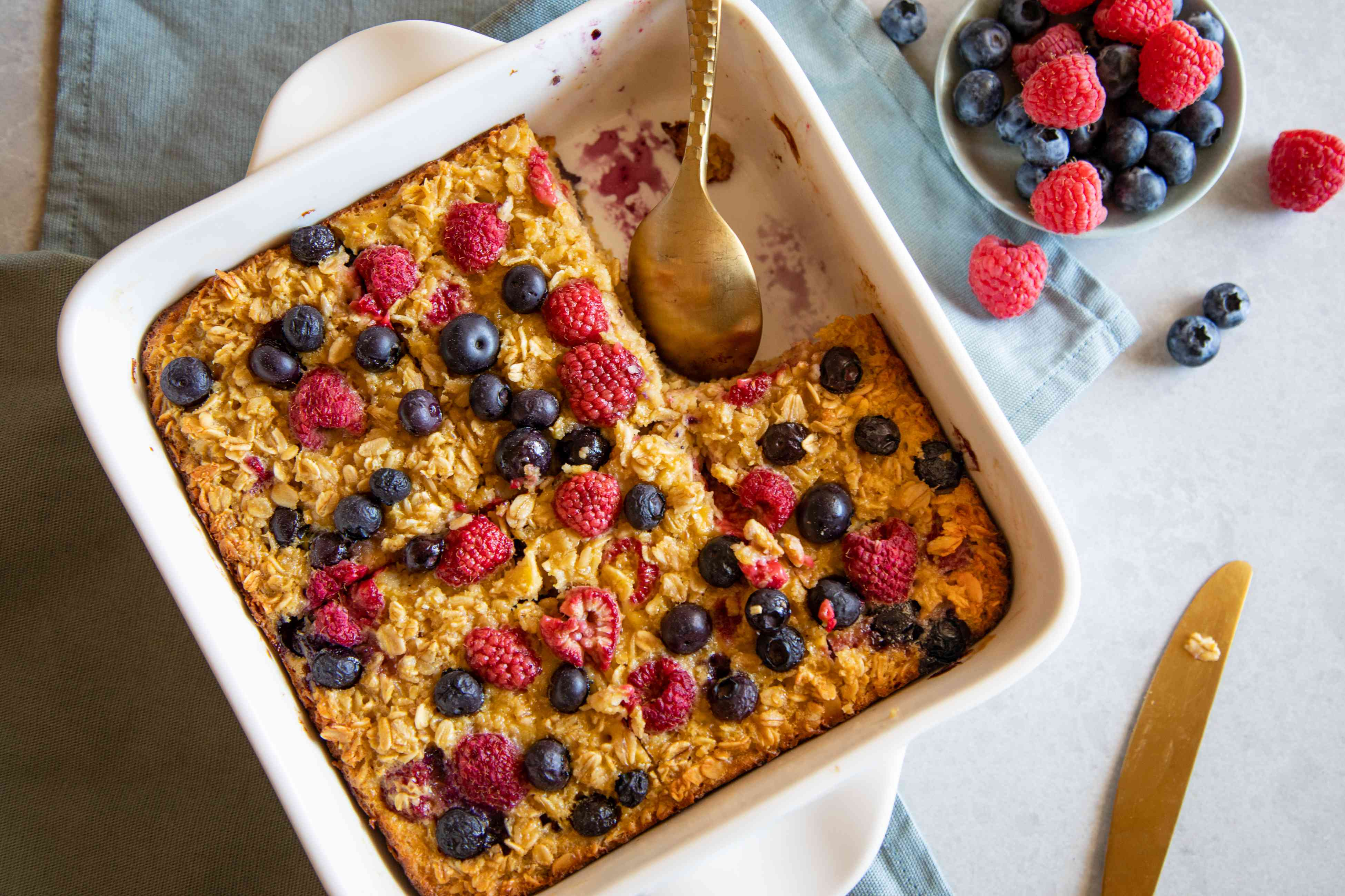 Overhead view of a baking pan with Baked Berry Oatmeal topped with extra berries with a serving removed from the dish.