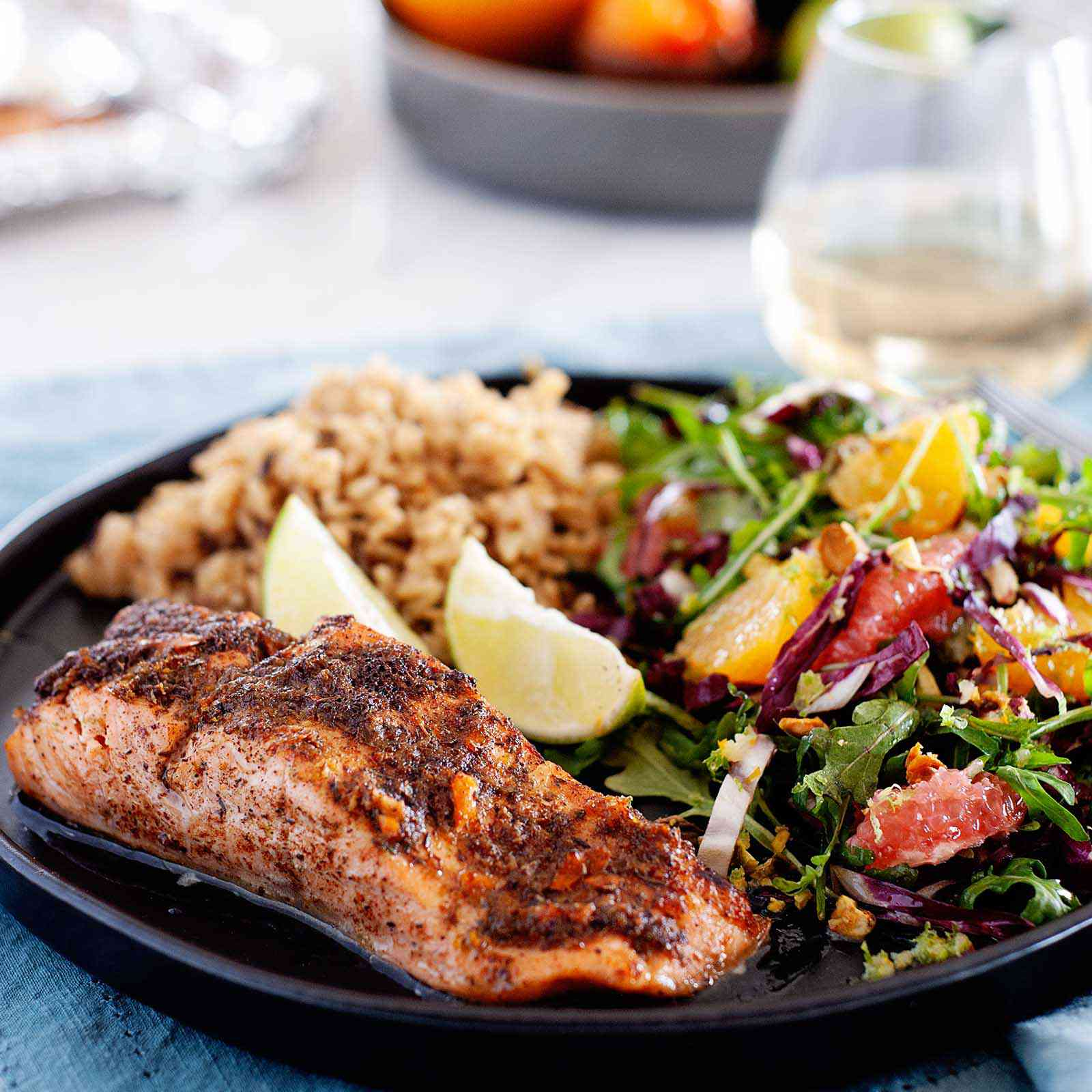 Side view of a fillet of broiled jerk salmon. The salmon has juices pooled at the bottom of it. A mixed green salad with citrus, two lime wedges and rice are visible on the plate behind the salmon. The plate is on a blue linen. Behind the plate is a glass of white wine, cutlery, a bowl of produce and the foil-lined baking sheet.