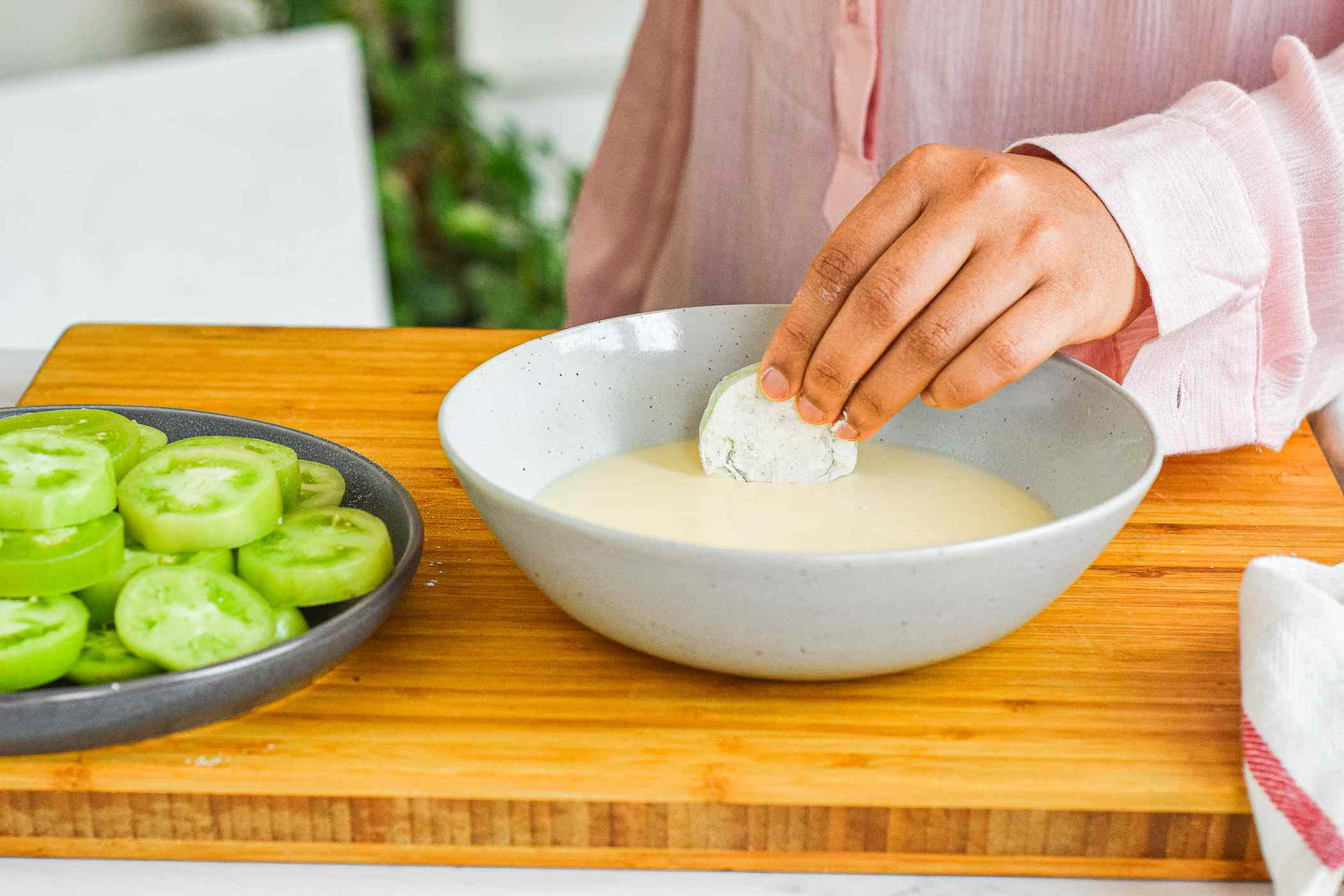 Dipping floured green tomato in egg mixture.