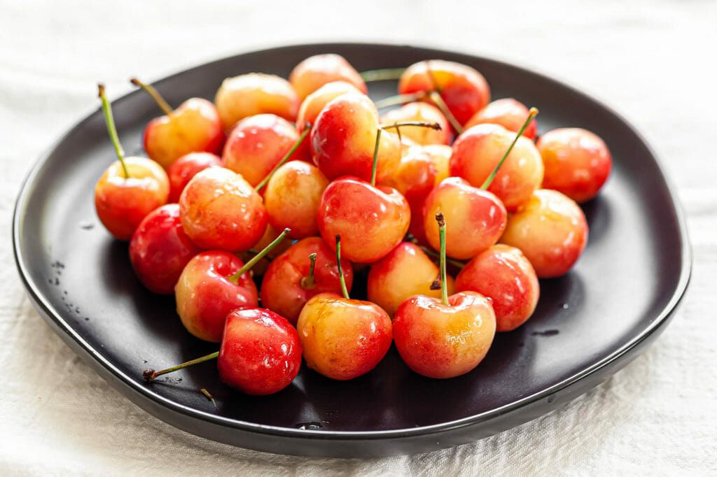 A dark plate with Rainier cherries piled in the center for a guide to cherries.