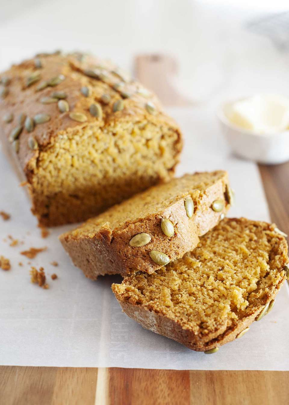 A loaf of the Best Vegan Pumpkin Bread cut into thick slices and set on a cutting board.
