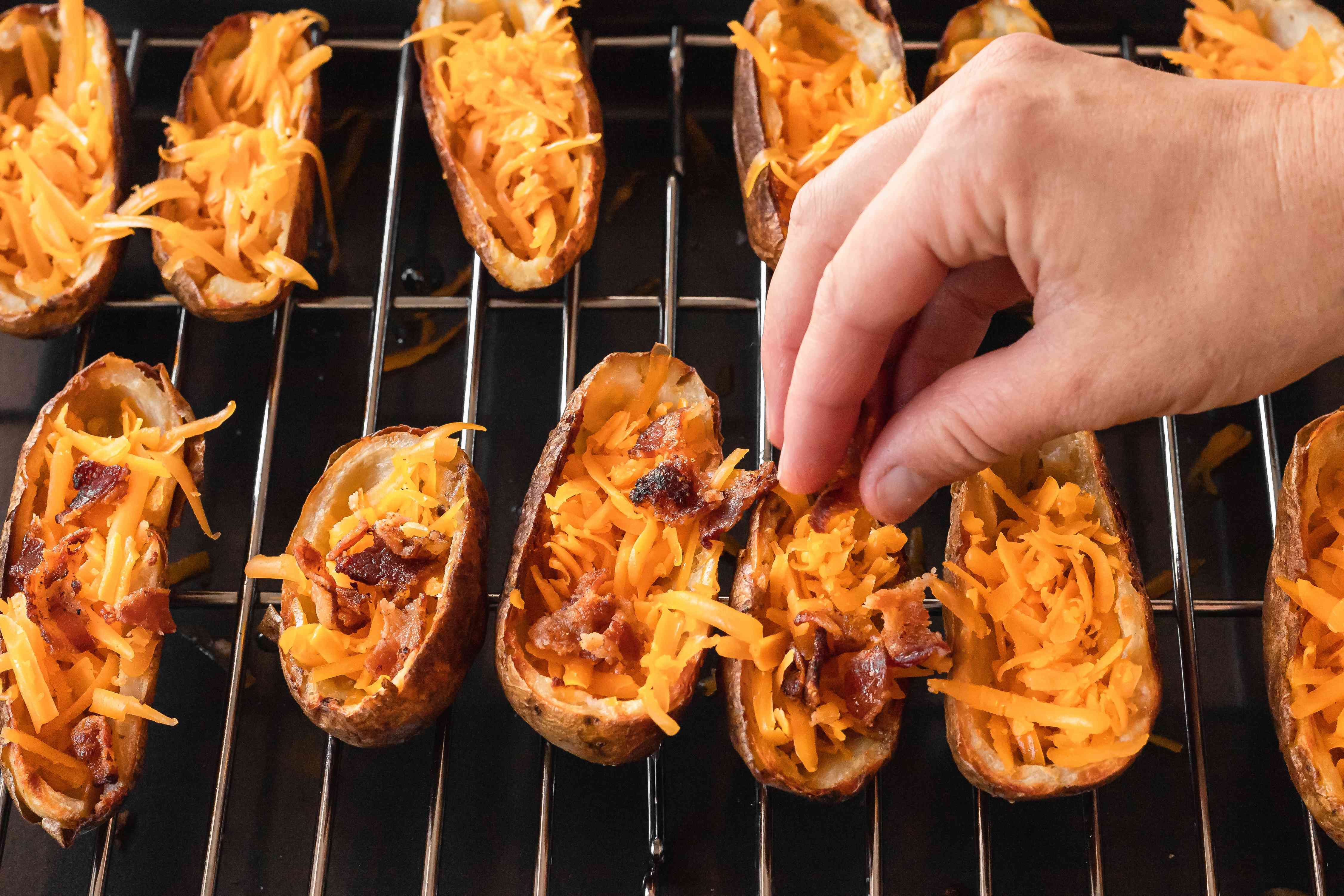 Topping potato skins with cheese and bacon.