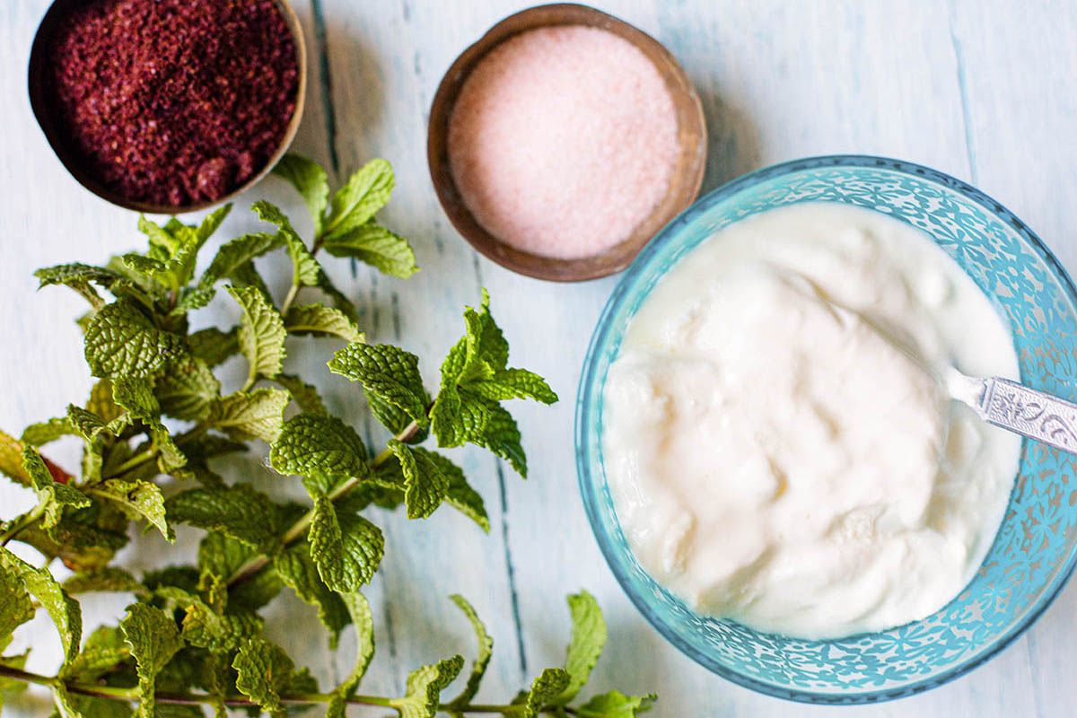 Yogurt dip in a blue bowl with fresh herbs nearby for easy Indian Samosas.