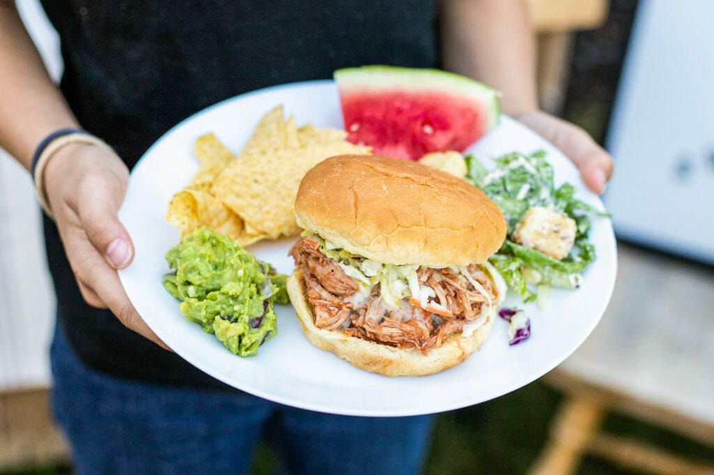 A person holding a plate with a BBQ sandwich, salad, chips and watermelon as part of the family activities.