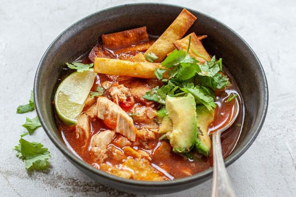 chicken tortilla soup served in a bowl with a spoon, topped with tortilla chips, lime, and cilantro