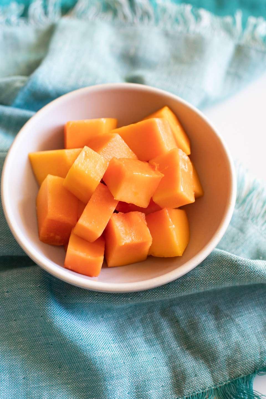 Cut papaya cubes in a white bowl on a blue napkin