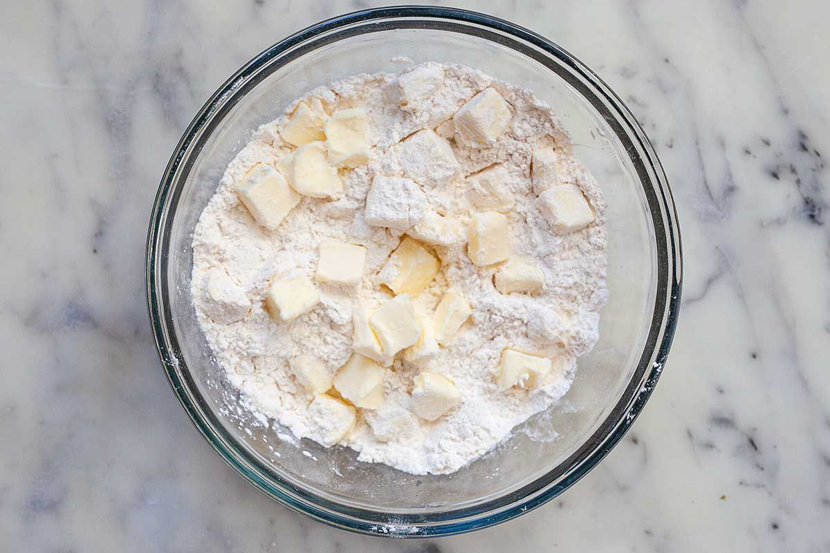 Cubes of butter are in a flour mixture inside a glass bowl on a marble countertop.