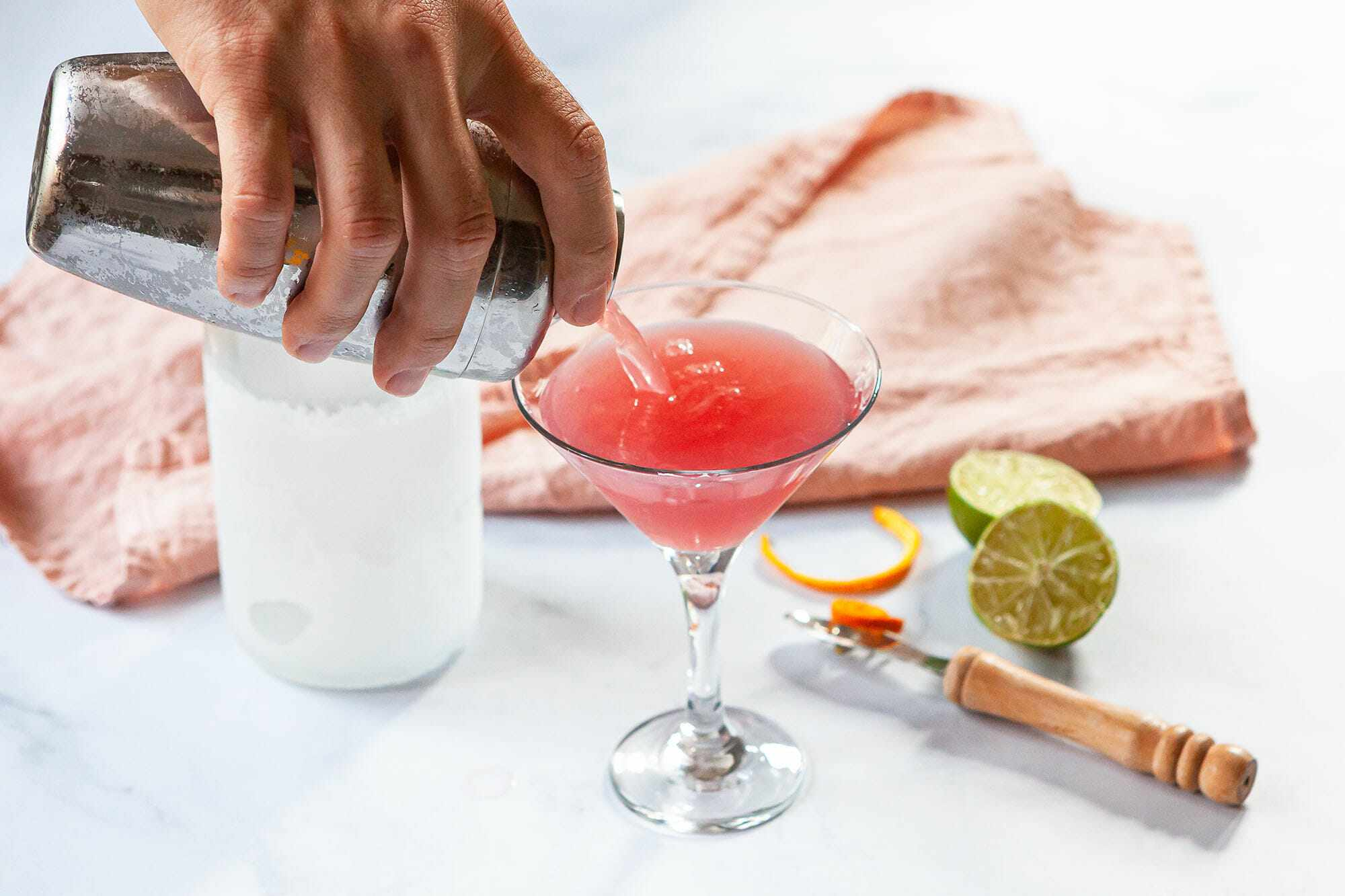 A cosmo recipe being made and poured into a martini glass.