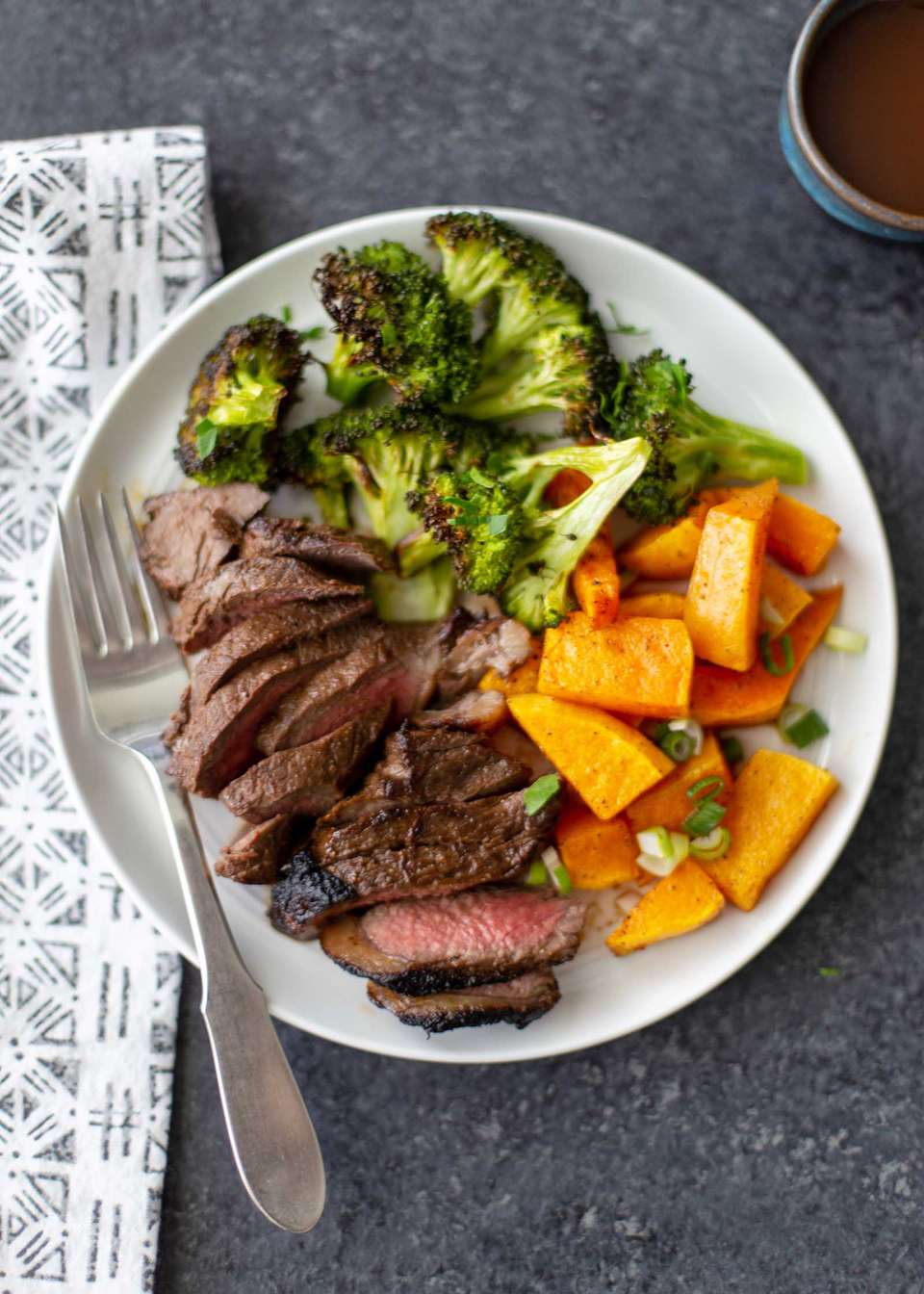 Sliced steak cooked in the stove on a white plate with seared edges and pink middle. Roasted broccoli and squash are on the plate.