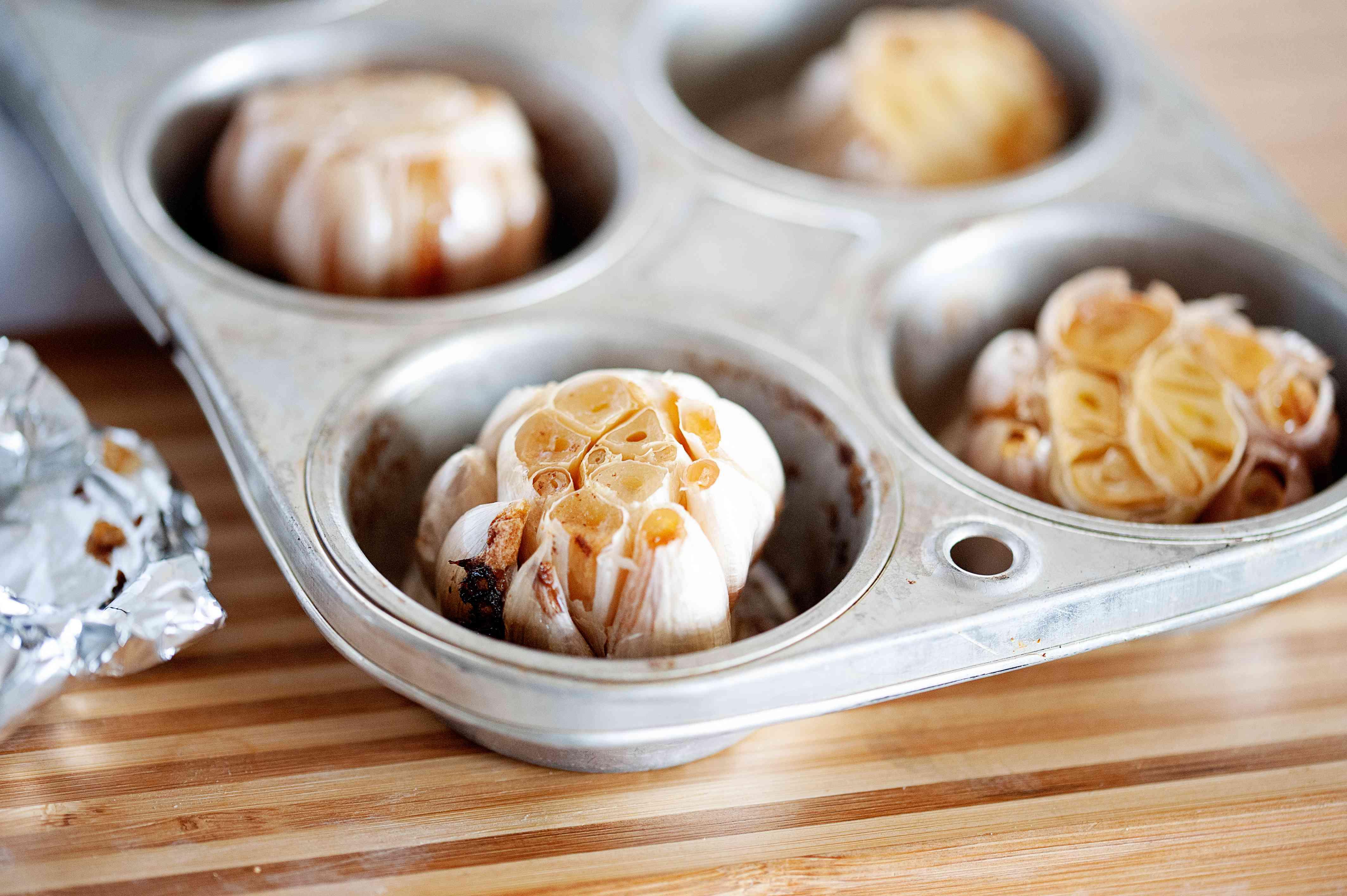 Roasted garlic cloves in a muffin tin.