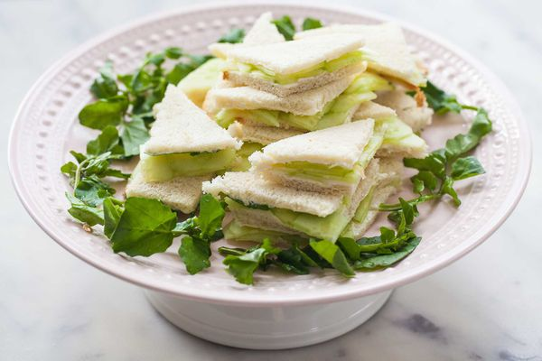 Triangle cut cucumber tea sandwiches are stacked on a cake stand and encircled with fresh herbs. Sliced cucucumbers are visible inside each one.