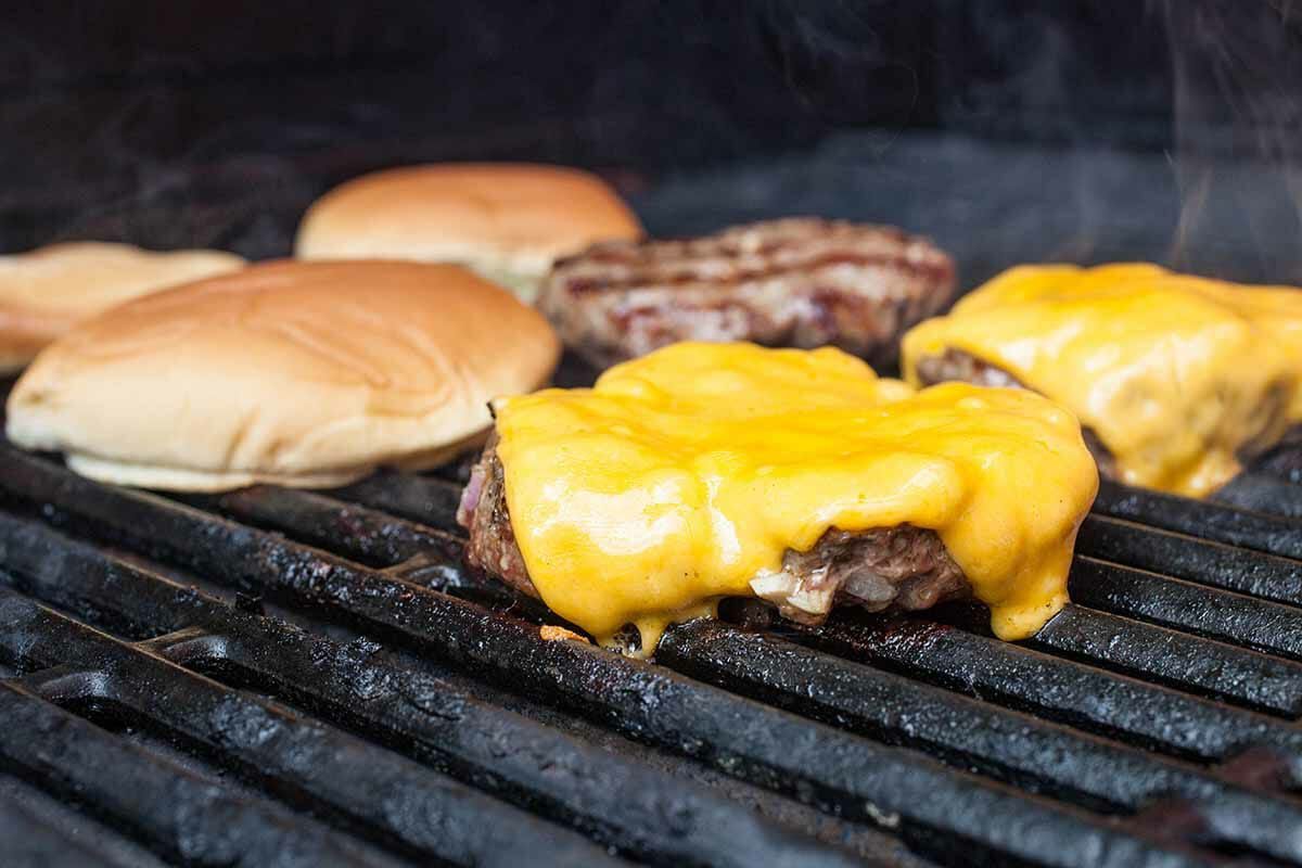 Melting cheese on burger with buns on grill