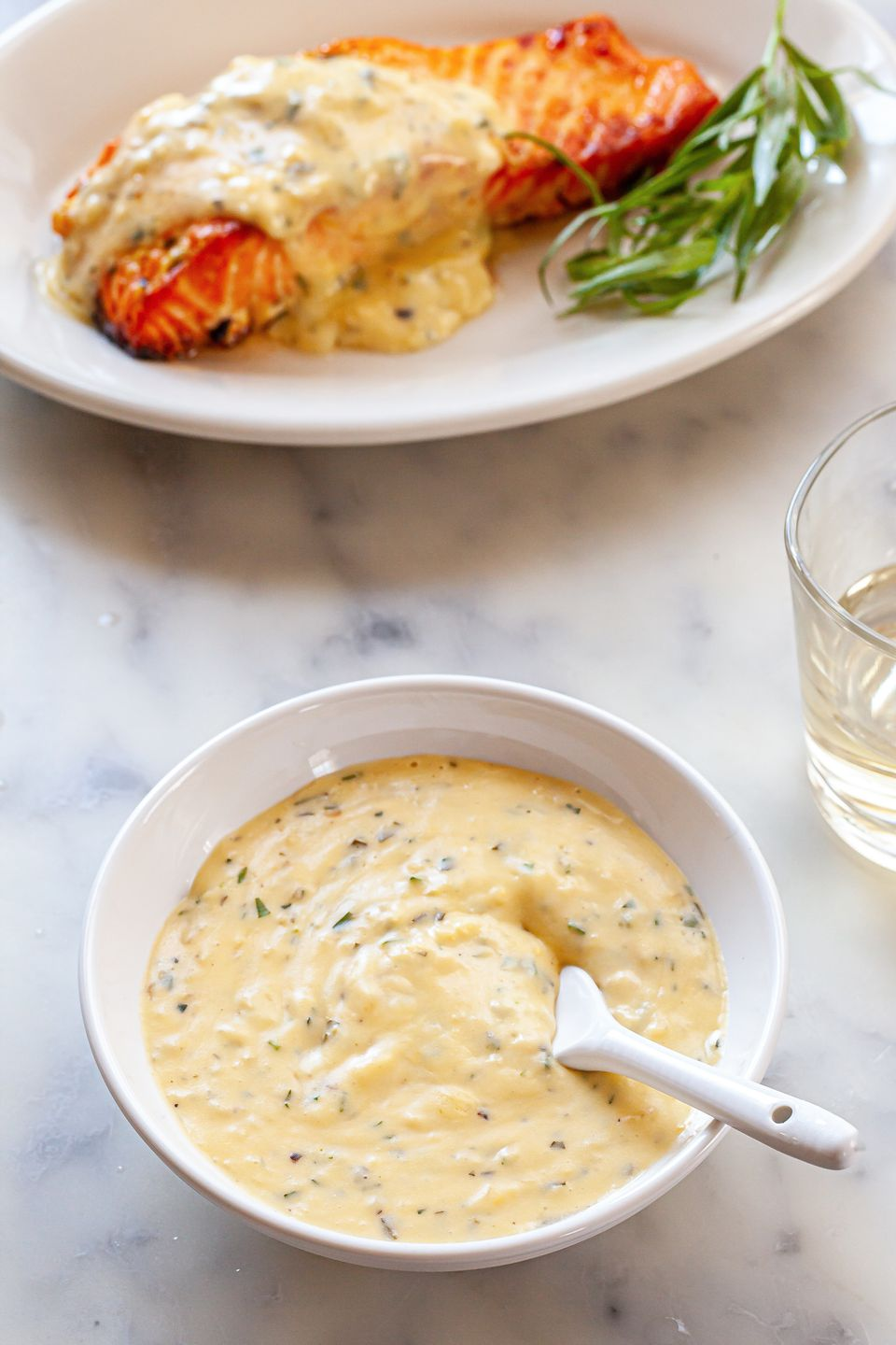 Classic mother sauce: béarnaise in a bowl with a plate of salmon and sauce set behind the bowl.