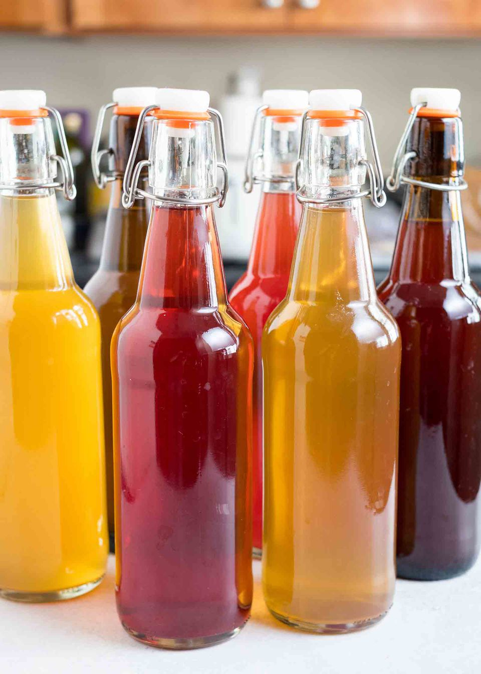 Several filled bottles of homemade kombucha on a counter