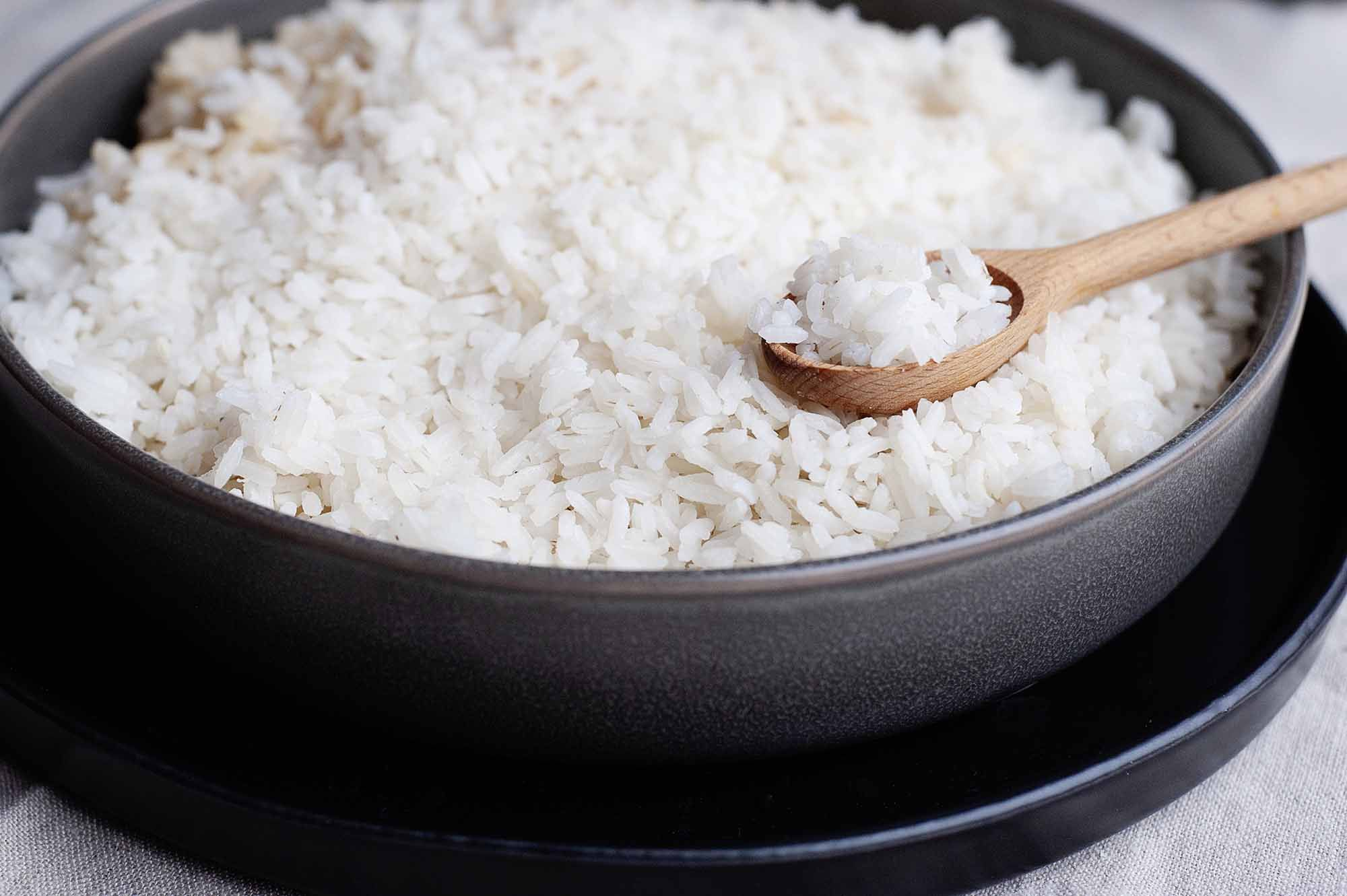 Perfect white rice in a metal pan with a wooden spoon full of cooked white rice.