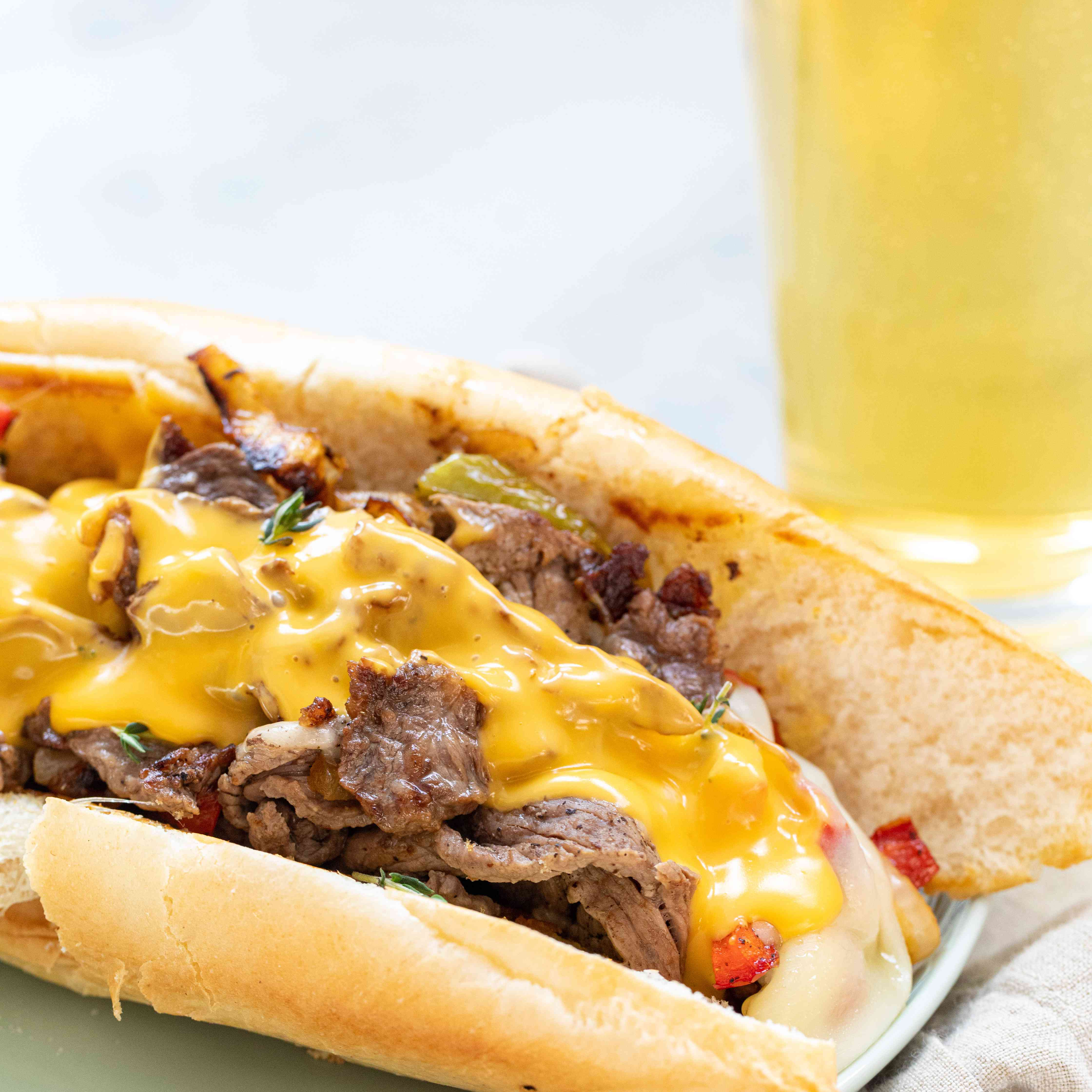 Philly Cheesesteak Sandwich with Onions and Peppers topped with cheese and on a plate.