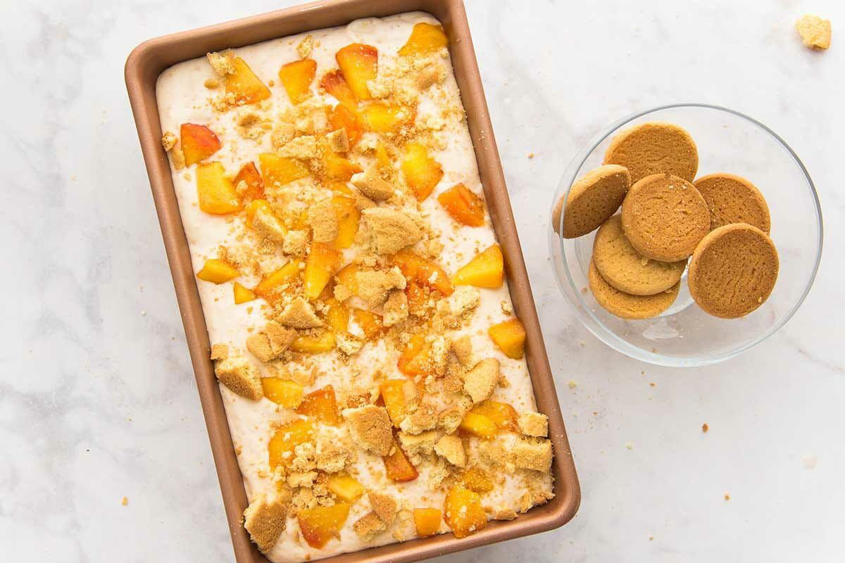 A loaf pan of easy peach cobbler ice cream being assembled. A bowl of vanilla wafers is set to the right.