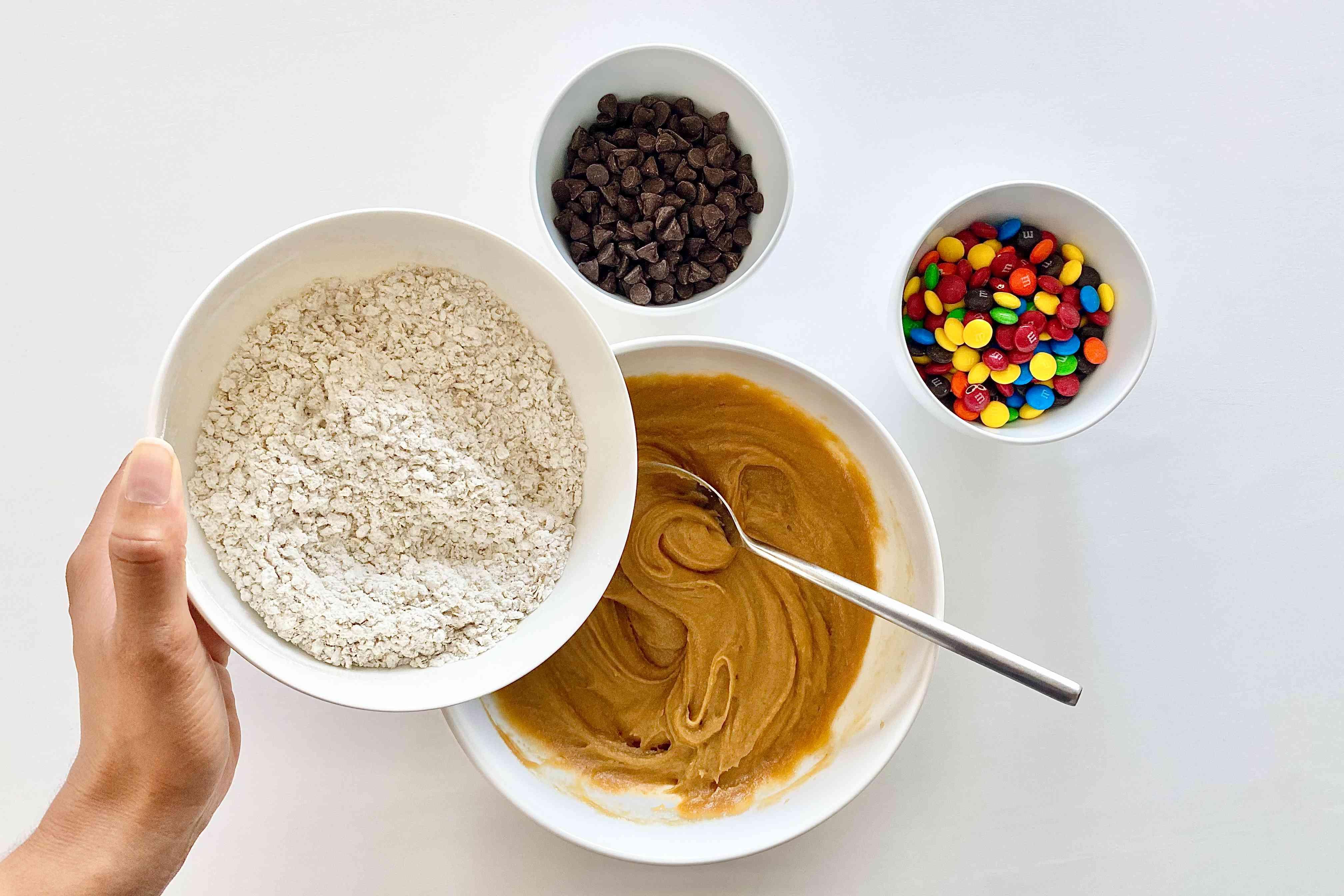 Adding flour mixture to wet mixture to make Gluten-Free Sheet Pan Monster Cookies.